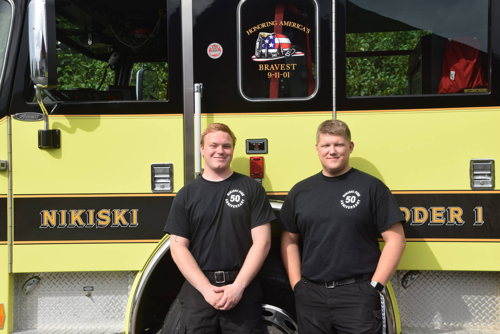 Volunteers Brandon Edwards, left, and Vlad Glushkov, right, smile for the camera at Fire Station #2 during the Nikiski Fire Department's 50th anniversary celebration in Nikiski, Alaska on July 15, 2019. (Photo by Brian Mazurek/Peninsula Clarion)
