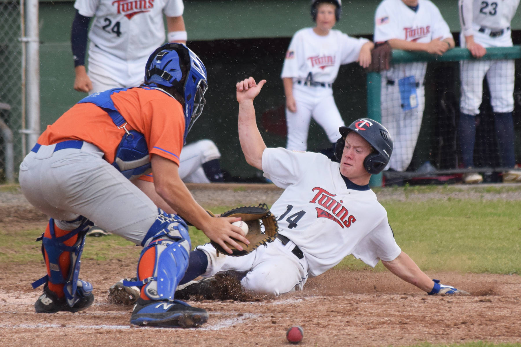 Twins pitcher Mose Hayes (14) slides safely into home ahead of the tag of Palmer catcher Brady Shults Tuesday, July 16, 2019, at Coral Seymour Memorial Park in Kenai, Alaska. (Photo by Joey Klecka/Peninsula Clarion)