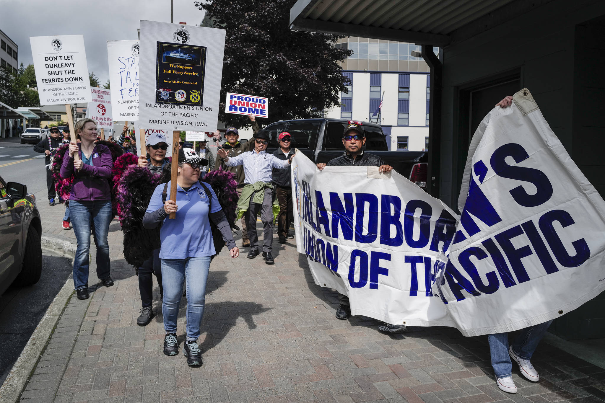 Backed by members of the Juneau Filipino community's Ati-Atihan musical group, members of the Inland Boatmen's Union of the Pacific march along Main Street in support of their continued strike against the Alaska Marine Highway System on Monday, July 29, 2019. (Michael Penn | Juneau Empire)