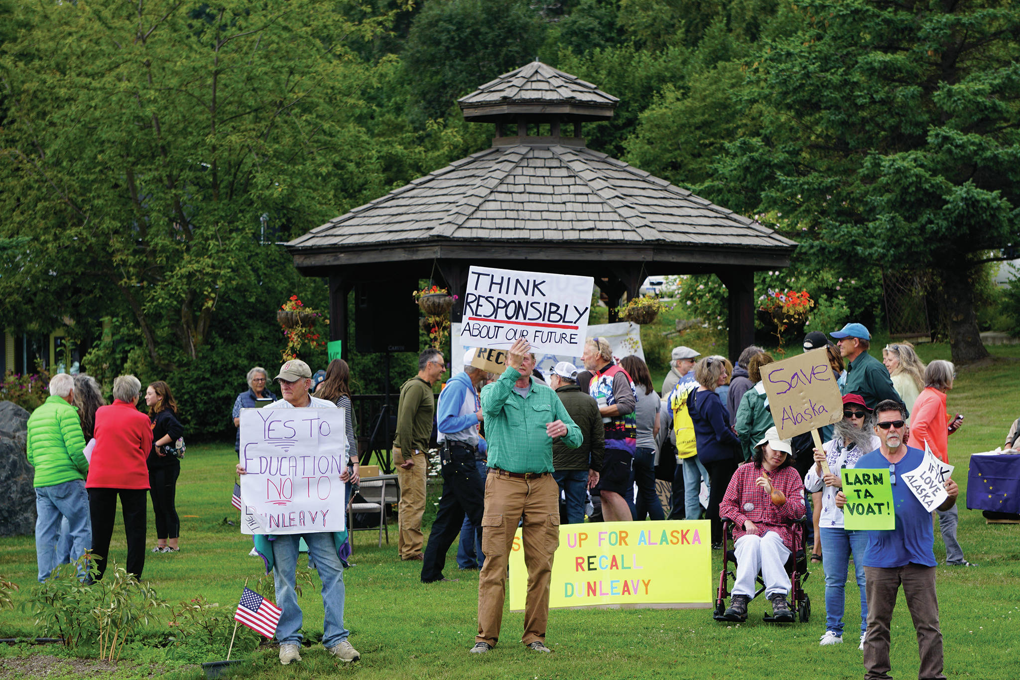 Recall Dunleavy supporters hold signs at a Recall Dunleavy rally held on Aug. 1, 2019, at WKFL Park in Homer, Alaska. (Photo by Michael Armstrong)