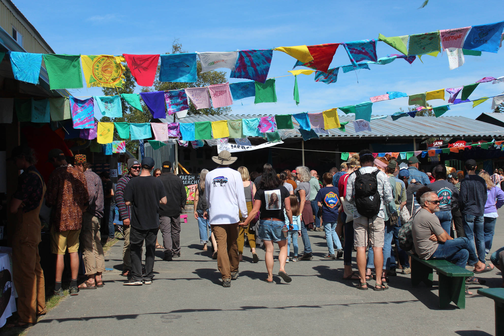 Festival goers walk through the Salmon Causeway — the collection of education and advocacy booths — on Friday, Aug. 2, 2019 at Salmonfest in Ninilchik, Alaska. (Photo by Megan Pacer/Homer News)