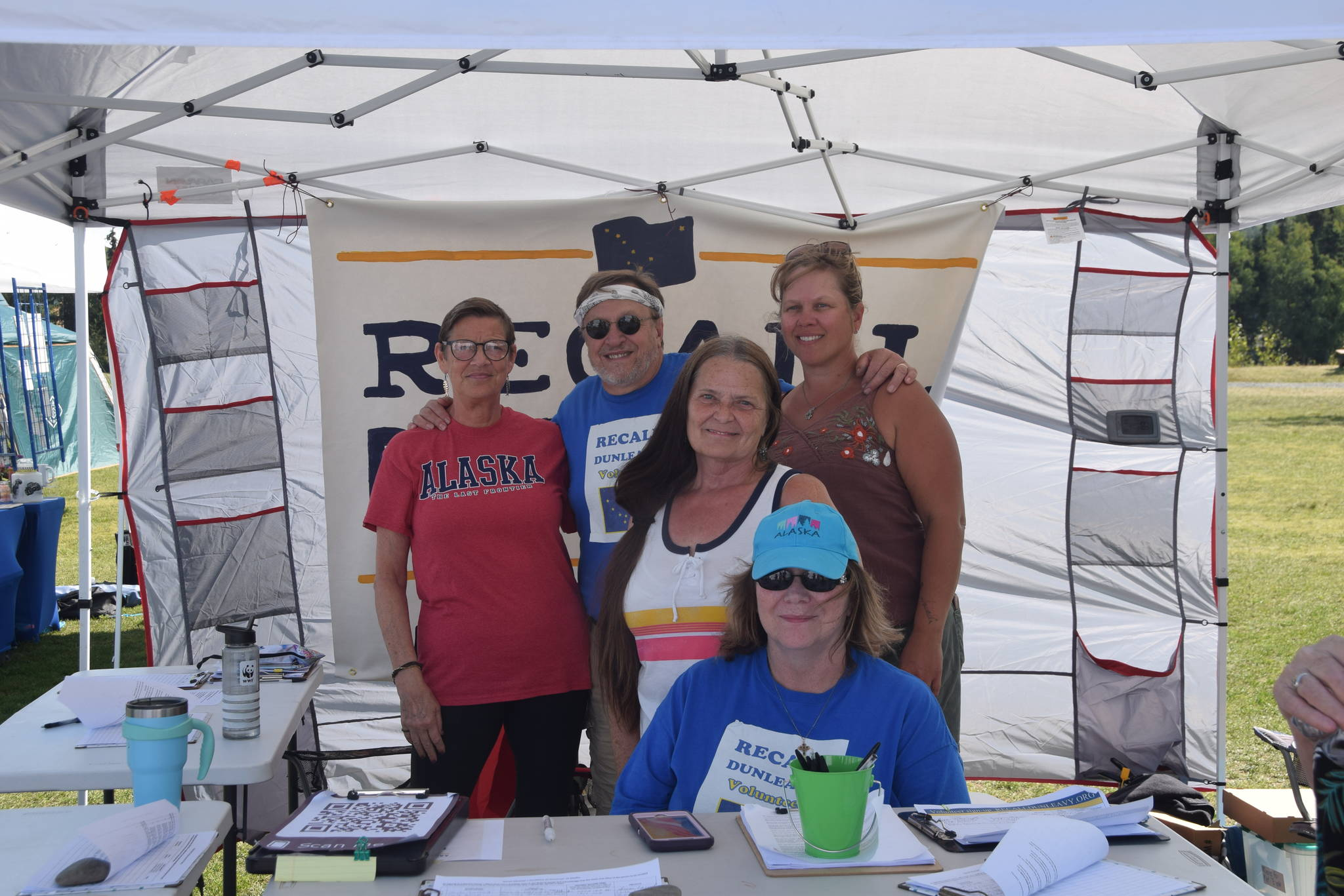 From left, Michele Vasquez, Eric Trieder, Fay Herold, Nelma Treider and Karyn Griffin smile for a photo while collecting signatures to recall Governor Mike Dunleavy in Soldotna Creek Park on Aug. 7, 2019. (Photo by Brian Mazurek/Peninsula Clarion)