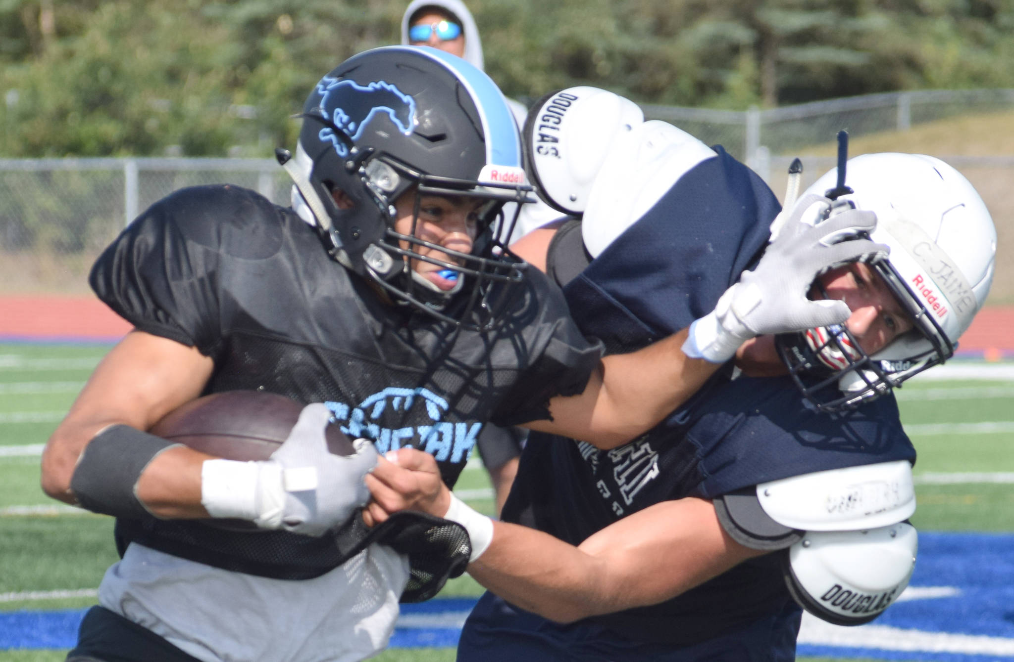 Chugiak's Tyler Huffer stiff-arms Soldotna's Hudson Metcalf during a scrimmage Saturday, Aug. 10, 2019, at Justin Maile Field in Soldotna, Alaska. (Photo by Jeff Helminiak/Peninsula Clarion)
