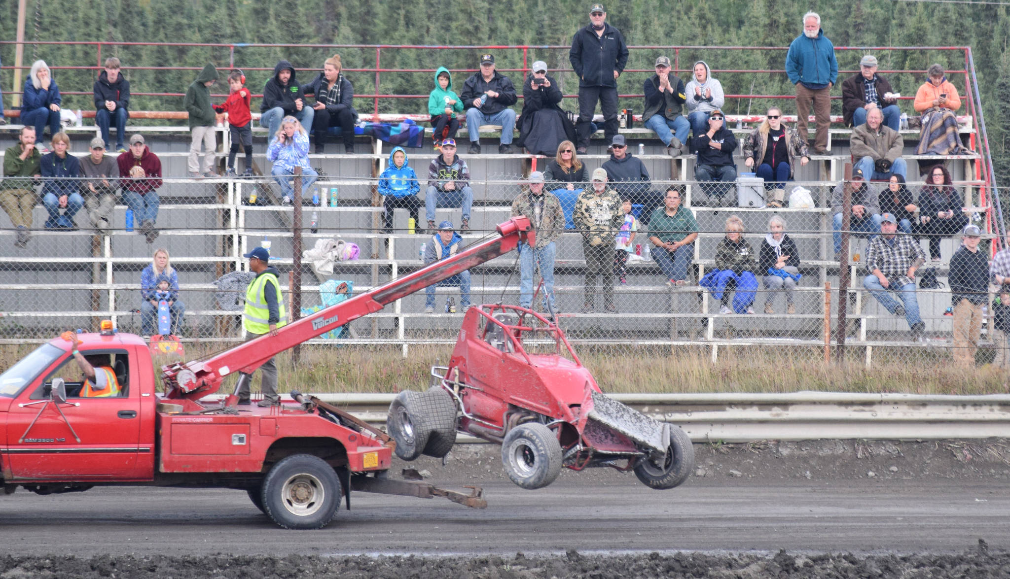 The crowd of race fans watch a tow truck pull the wrecked Sprint Car of John Mellish away Friday, Sept. 6, 2019, at Twin City Raceway in Kenai, Alaska. Mellish was unhurt in the incident. (Photo by Joey Klecka/Peninsula Clarion)