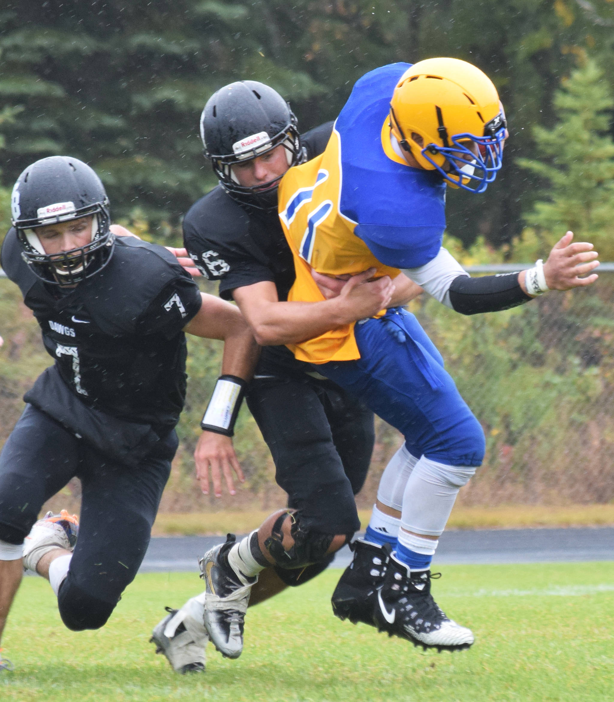 Nikiski's Caileb Payne (left) wraps up Barrow running back Ervin Feleti for a tackle Saturday, Sept. 7, 2019, in Nikiski, Alaska. (Photo by Joey Klecka/Peninsula Clarion)