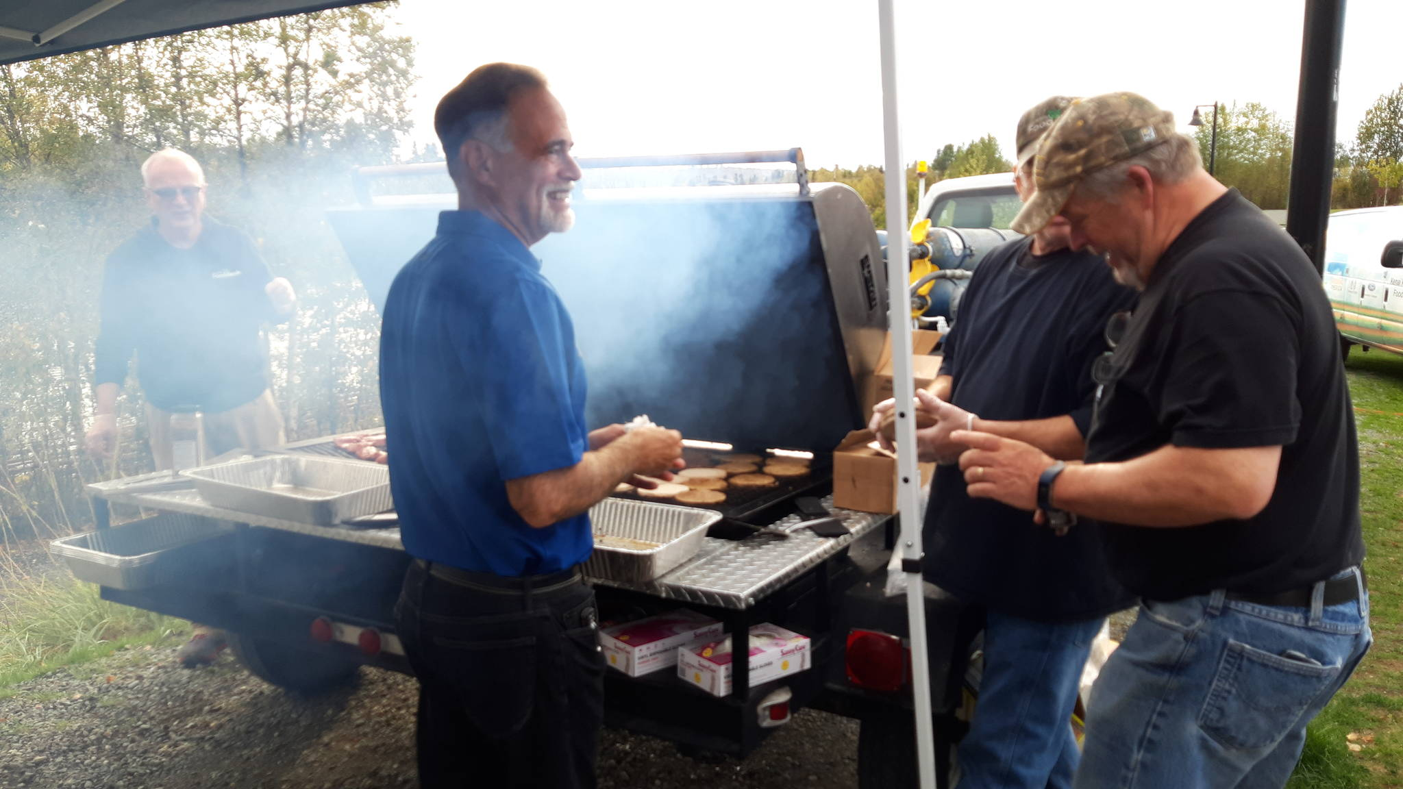 Sen. Peter Micciche, R-Soldotna, mans the grill with other volunteers during the first responder appreciation barbecue at Soldotna Creek Park on Monday, Sept. 9, 2019 in Soldotna, Alaska. (Photo by Brian Mazurek/Peninsula Clarion)
