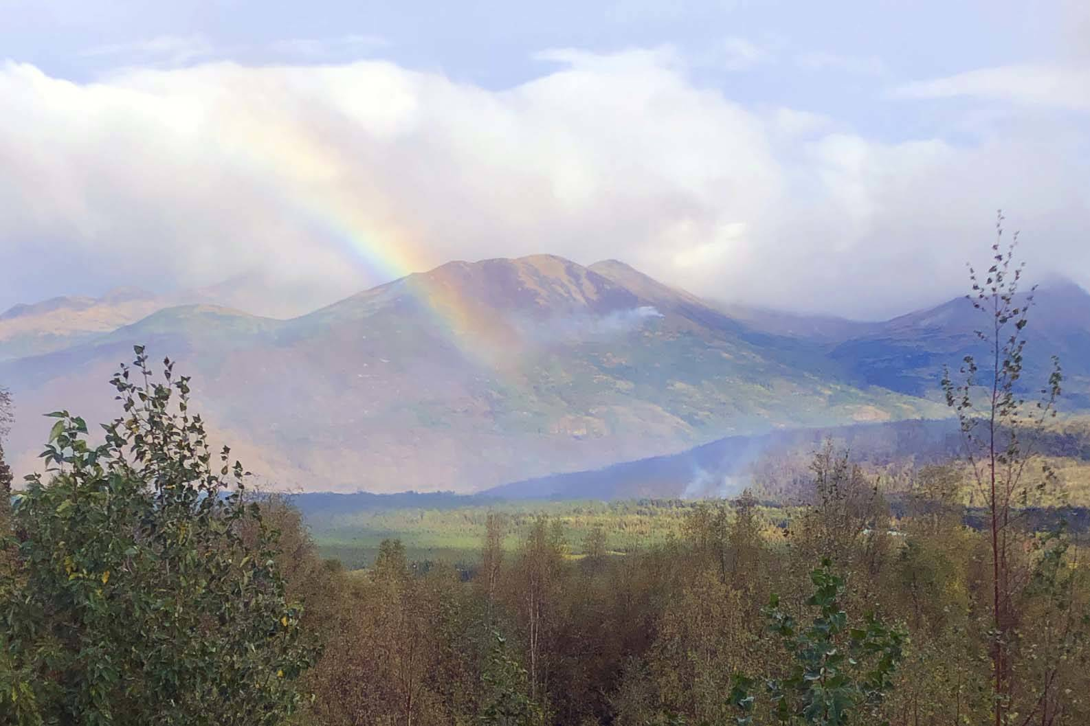 Courtesy Kenai Peninsula Borough Office of Emergency Management                                 A rainbow can be seen next to rising smoke from the Swan Lake Fire in this photo released Thursday, Sept. 5.