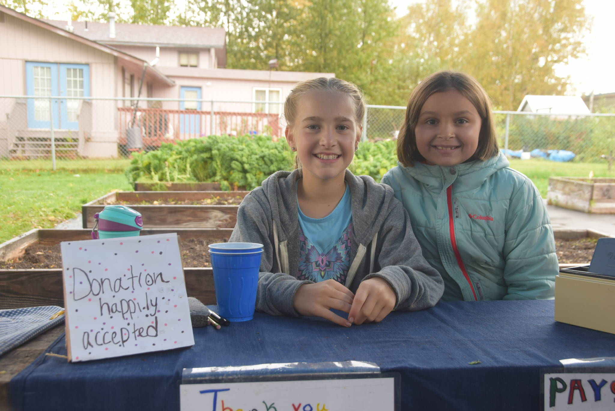 Katie Debardelaben, left, and Aurora Oostman, right, hold down the cash register at the Montessori Farmer's Market at the Soldotna Montessori School on Sept. 13, 2019. (Photo by Brian Mazurek/Peninsula Clarion)
