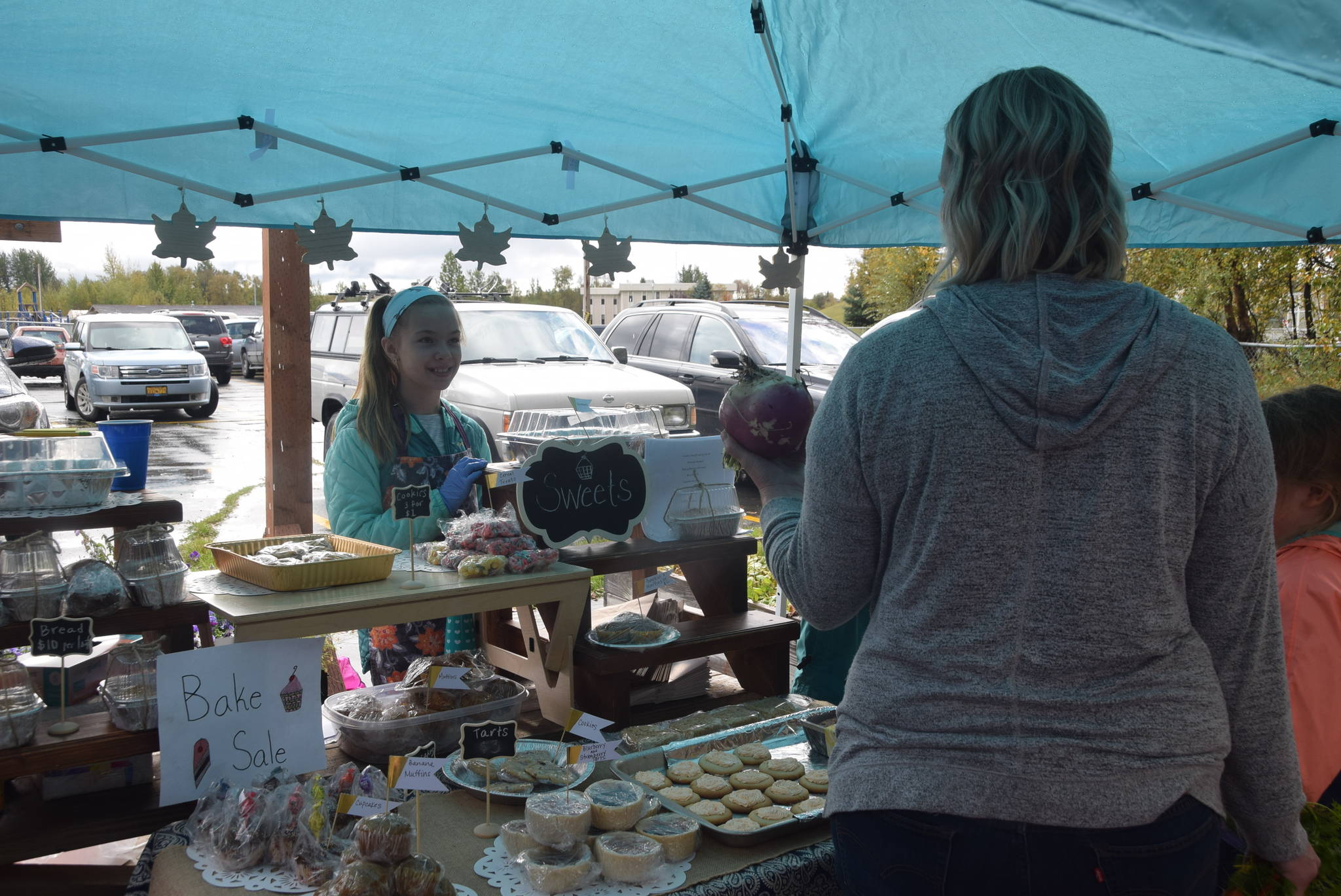 Kaitlyn Miller makes a sale at the baked goods station during the Montessori Farmer's Market at the Soldotna Montessori School on Sept. 13, 2019. (Photo by Brian Mazurek/Peninsula Clarion)