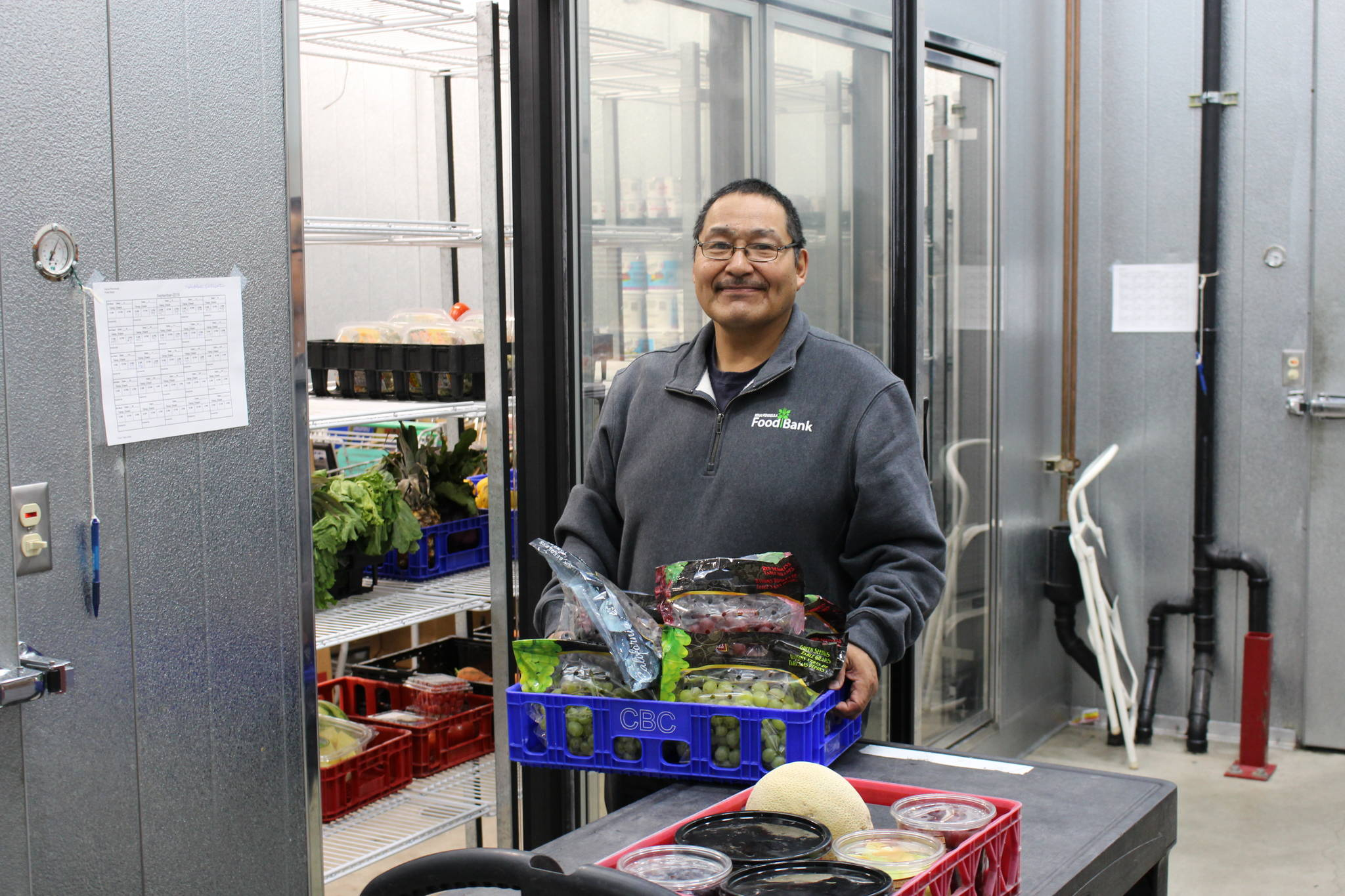 Food Bank employee Francis Bell stocks up the cooler at the Kenai Peninsula Food Bank in Soldotna, Alaska on Sept. 20, 2019. (Photo by Brian Mazurek/Peninsula Clarion)