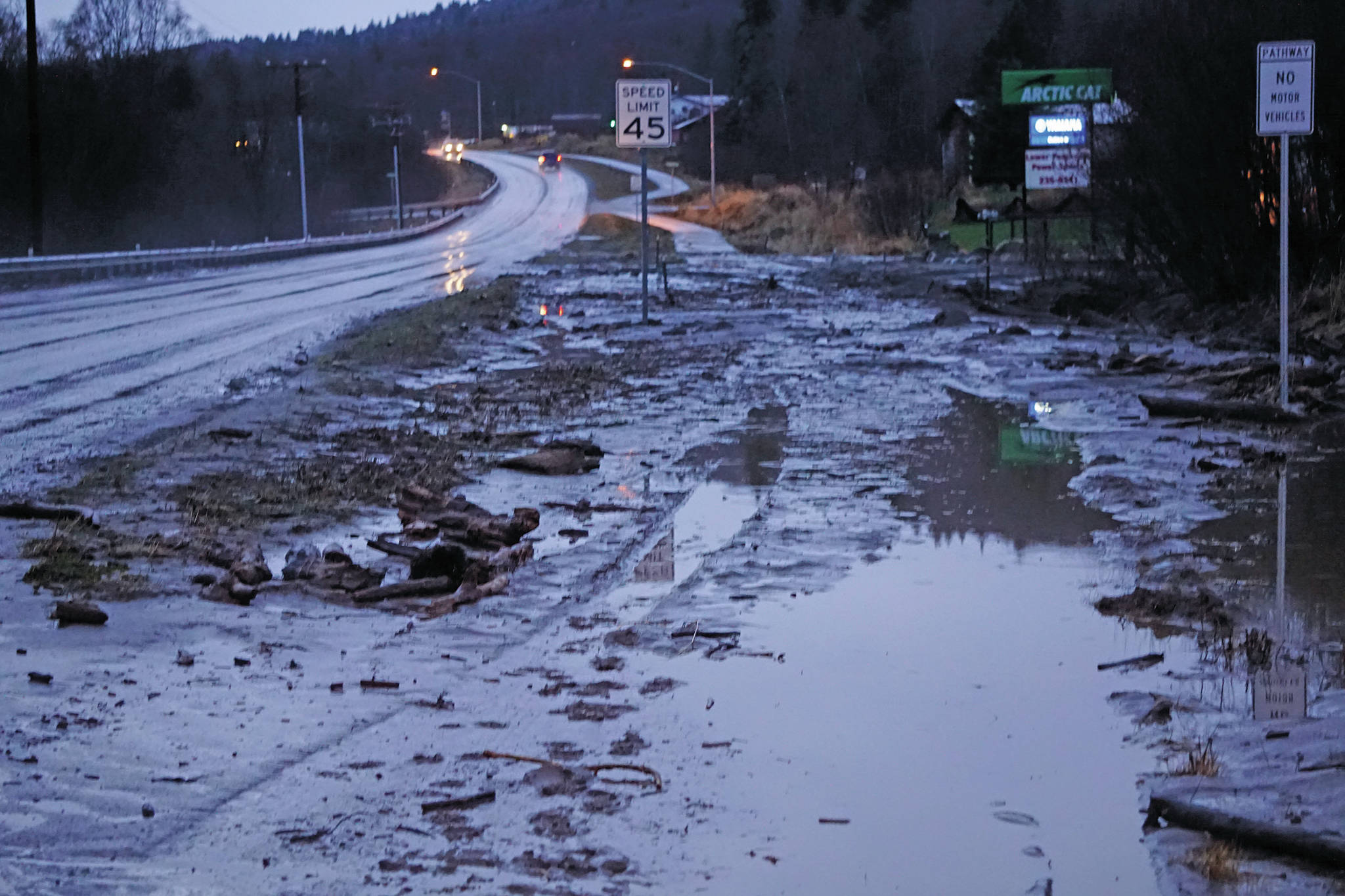 Mud and debris is washed up at Bear Creek near East End Road on Monday afternoon, Dec. 9, 2019, in Homer, Alaska. Bear Creek crosses East End Road near Bear Creek Drive and overflowed the creek banks. (Photo by Michael Armstrong/Homer News)