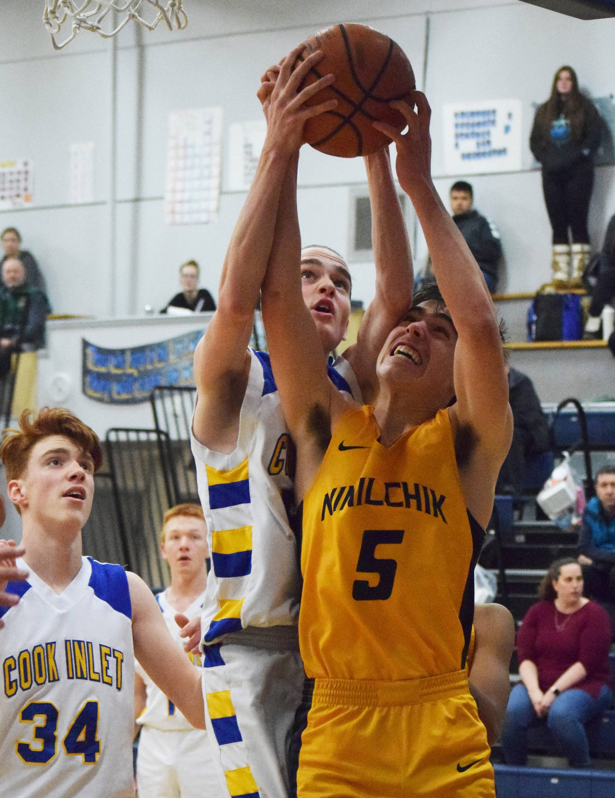 Ninilchik's Tom Nelson (5) gets a block from CIA's Josh Boyd, Tuesday, Jan. 7, 2020, at Cook Inlet Academy in Soldotna, Alaska. (Photo by Joey Klecka/Peninsula Clarion)