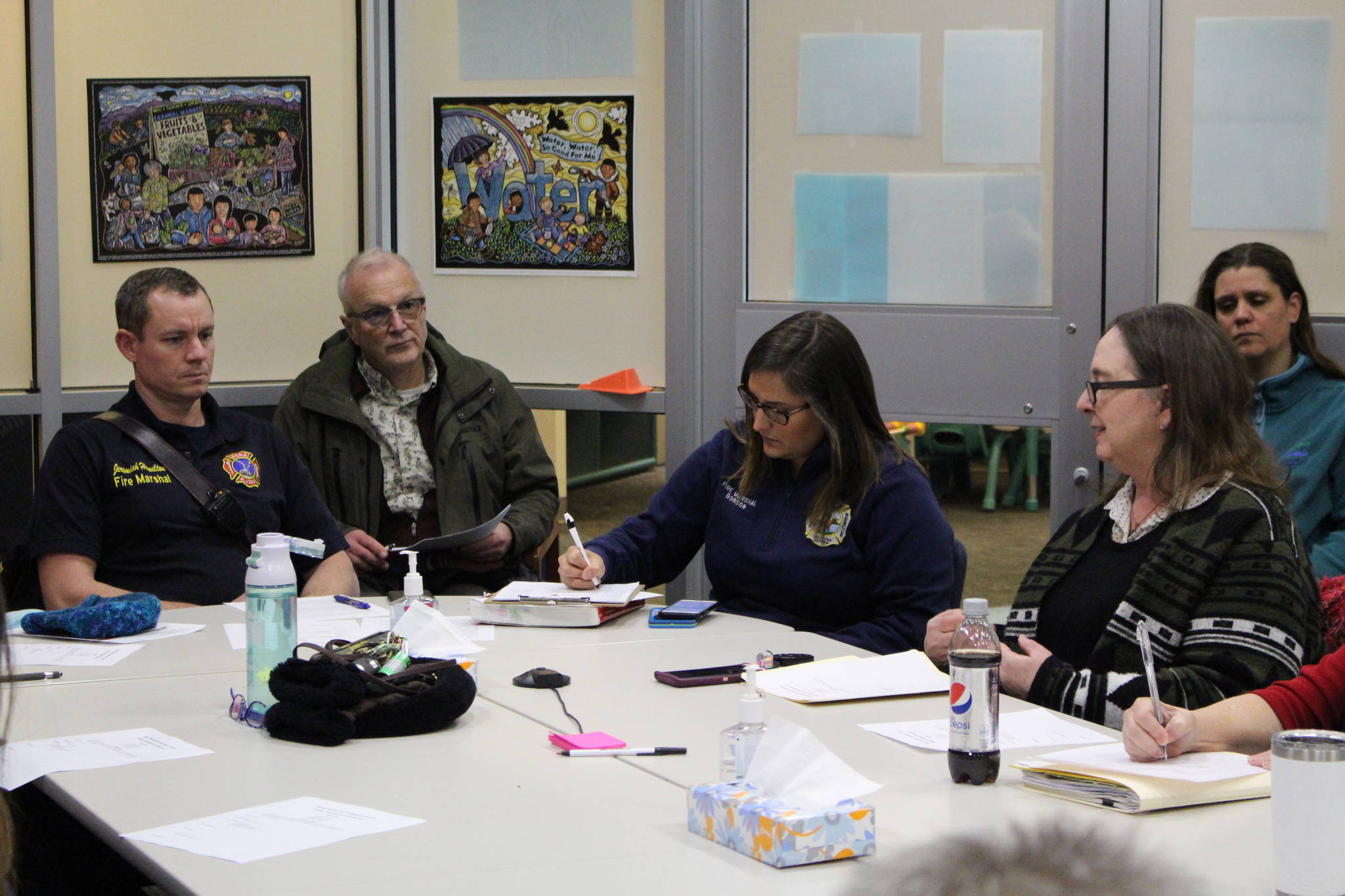 Brian Mazurek / Peninsula Clarion                                 Fire Marshals Jeremy Hamilton (left) and Brooke Dobson (center right) meet with members of the Shelter Development Workgroup at the Kenai Public Health Center in Kenai on Jan. 8.