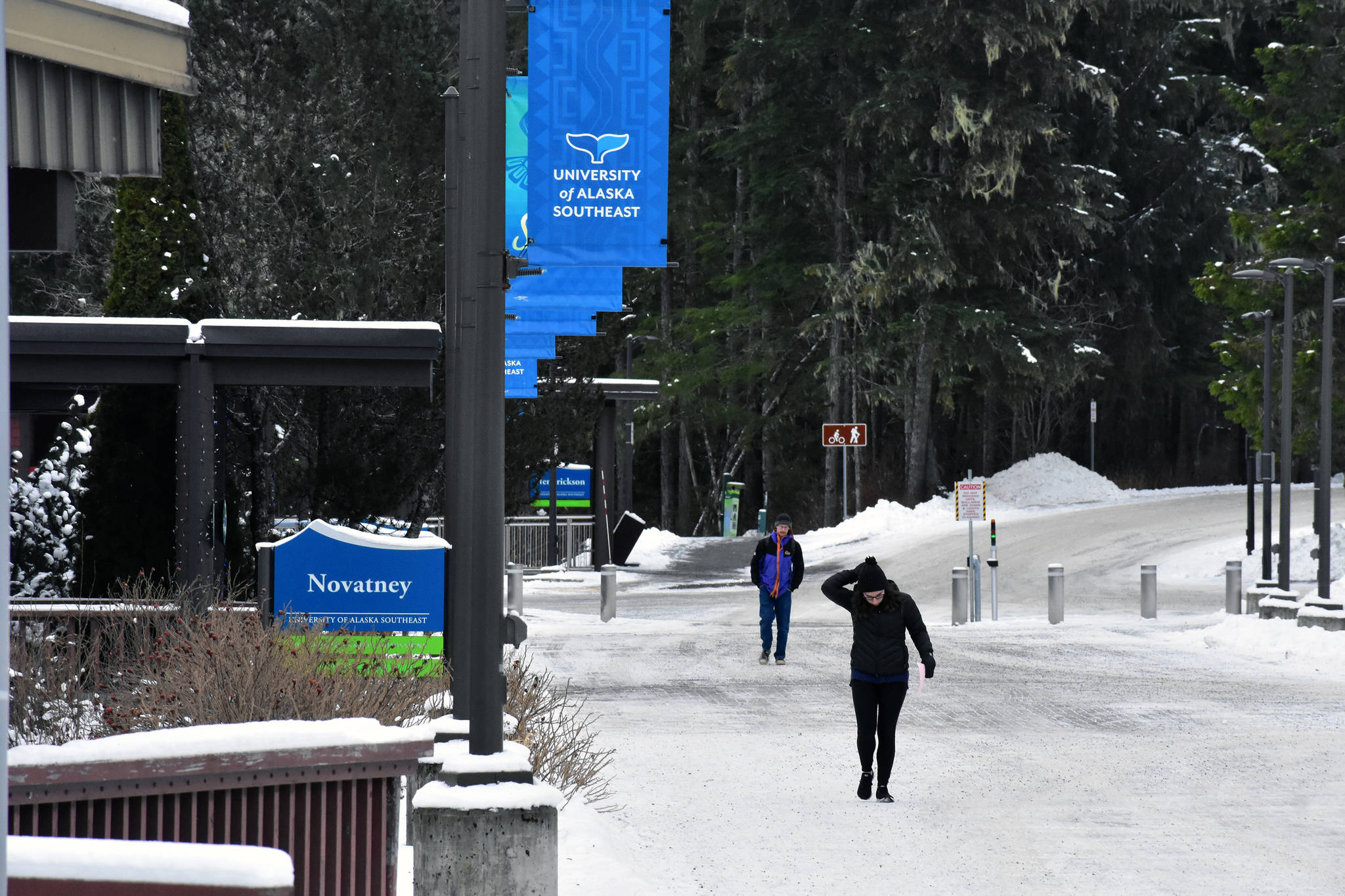 A student fixes her hood as she walks across the campus at the University of Alaska Southeast on Thursday, Jan. 16, 2020. (Peter Segall | Juneau Empire)