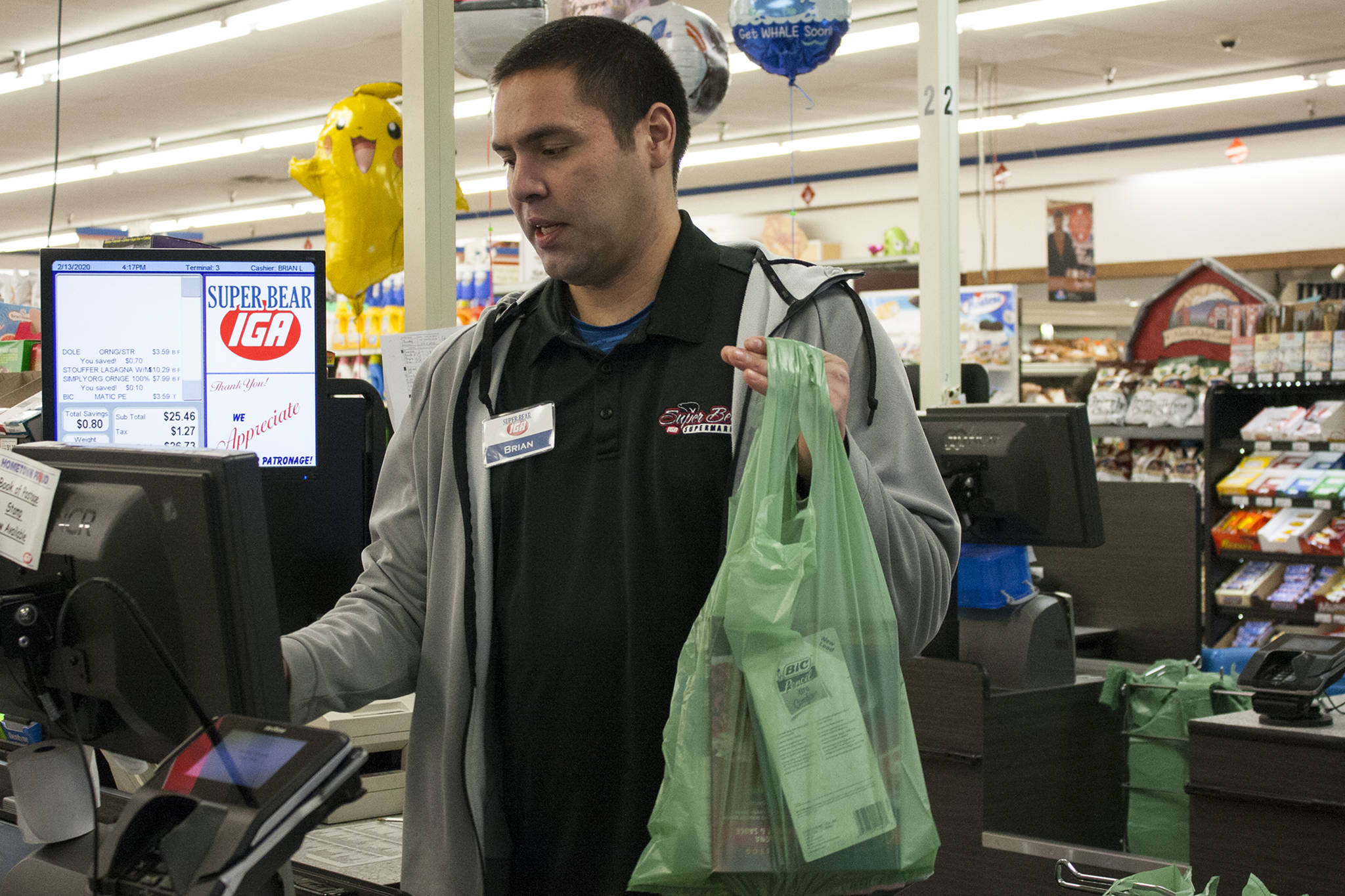 Brian Lauth, closing manager for Super Bear Supermarket IGA, bags groceries Thursday, Feb. 13, 2020. Super Bear will be collecting donations to ship food to Southeast Alaska communities impacted by a lack of ferry service. (Ben Hohenstatt | Juneau Empire)