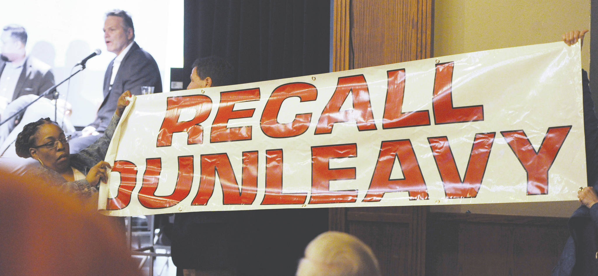 In this March 26, 2019, file photo, protesters unfurl a banner as Alaska Gov. Mike Dunleavy speaks during a roadshow with Americans for Prosperity in 49th State Brewing Company in Anchorage. The group opposing an effort to recall Alaska Gov. Mike Dunleavy plans to drop its court fight and instead gear up for a possible recall election. Stand Tall With Mike said Tuesday, Feb. 18, 2020, that it told its attorneys to withdraw its appeal before the Alaska Supreme Court. The group says recent court actions indicate that continuing to pursue the case in court would not be a productive use of resources. (Bill Roth/Anchorage Daily News via AP, File)