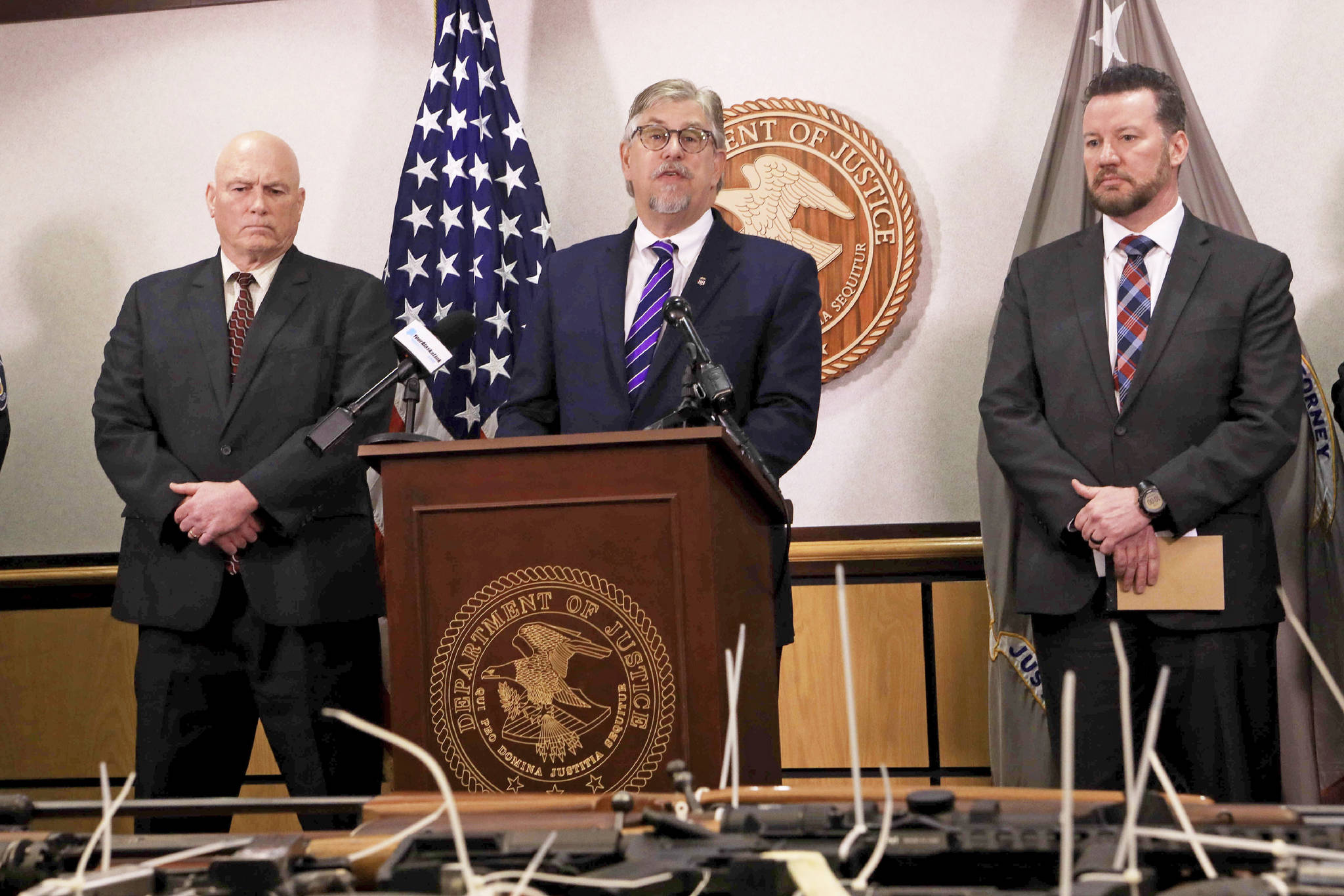 Bryan Schroder, center, U.S. attorney for Alaska, speaks at a press conference announcing the seizure of 82 illegally possessed guns in Anchorage and surrounding communities on Wednesday, Feb. 26, 2020, in Anchorage, Alaska. U.S Marshal Rob Heun, left, and Darek Pleasants of the Bureau of Alcohol, Tobacco and Firearms, right, look on. The investigation resulted in federal charges against 16 people for firearm or drug trafficking counts. (AP Photo/Dan Joling)