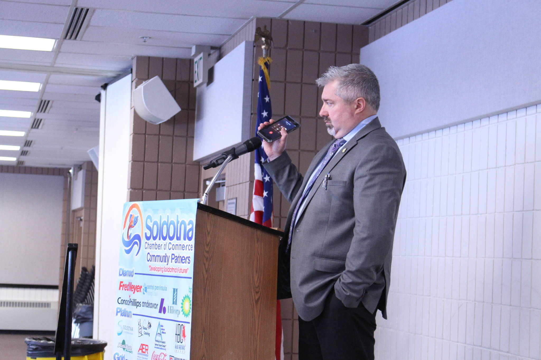 Dave Stieren, community outreach director for Gov. Mike Dunleavy, holds his phone up to the microphone as Dunleavy gives a remote speech to the Kenai and Soldotna Chambers of Commerce at the Soldotna Regional Sports Complex on March 9, 2020. (Photo by Brian Mazurek/Peninsula Clarion)
