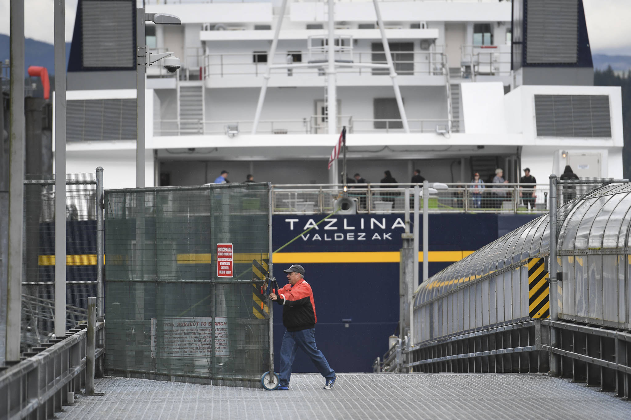 The Alaska Marine Highway System employee opens the vehicle gate after the Tazlina arrives at the Auke Bay Terminal in July 2019. (Michael Penn | Juneau Empire File)