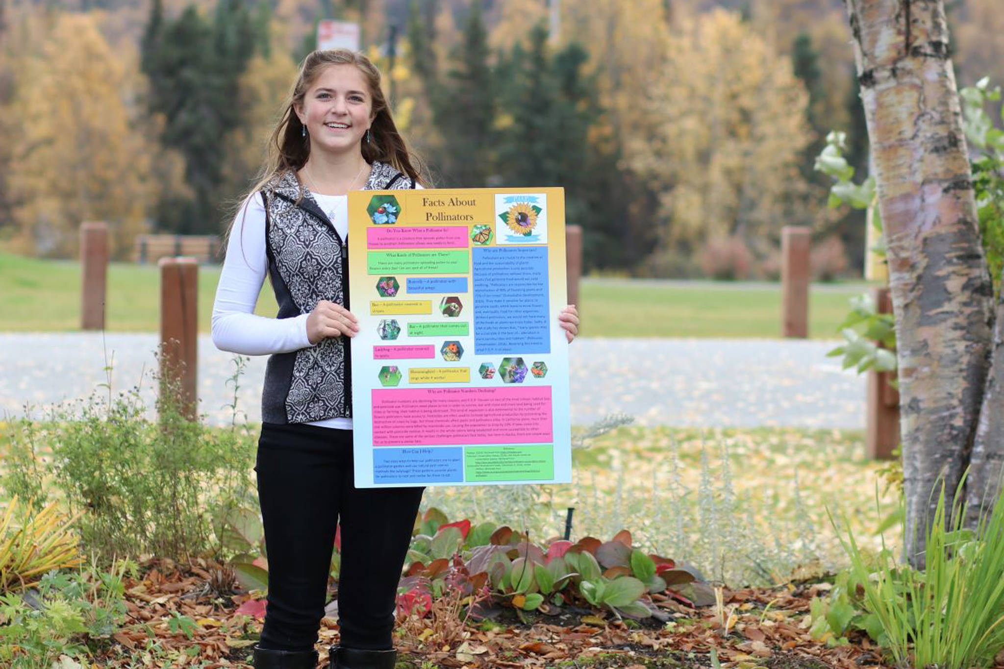 Anna DeVolld poses with an informational poster for her Promote Our Pollinators project in this undated photo. (Photo courtesy Shona DeVolld)