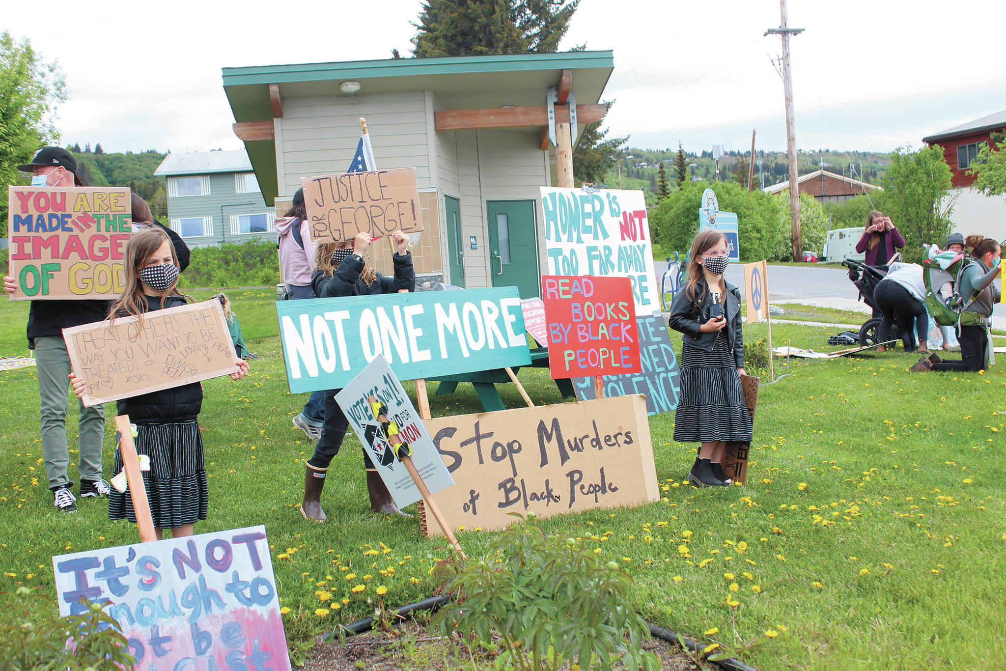 Families and their children wave to drivers from a Black Lives Matter demonstgration at WKFL Park on Tuesday, June 2, 2020 in Homer, Alaska. (Photo by Megan Pacer/Homer News)