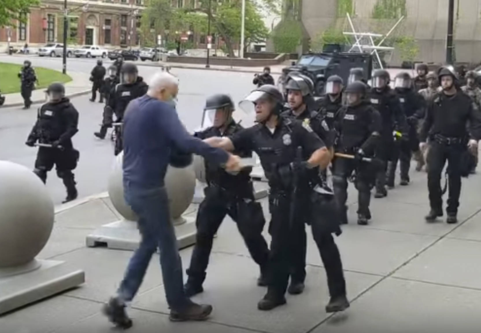 """In this image from video provided by WBFO, a Buffalo police officer appears to shove a man who walked up to police Thursday, June 4, 2020, in Buffalo, N.Y. Video from WBFO shows the man appearing to hit his head on the pavement, with blood leaking out as officers walk past to clear Niagara Square. Buffalo police initially said in a statement that a person """"was injured when he tripped & fell,"""" WIVB-TV reported, but Capt. Jeff Rinaldo later told the TV station that an internal affairs investigation was opened. Police Commissioner Byron Lockwood suspended two officers late Thursday, the mayor's statement said. (Mike Desmond 