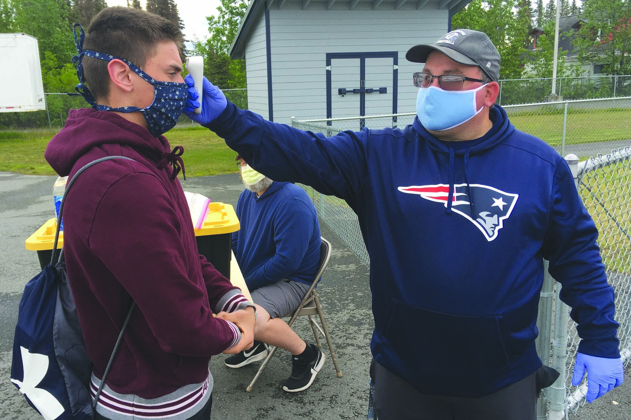 Soldotna assistant football coach Eric Pomerleau checks the temperature of sophomore Joseph Whittom before summer workouts Wednesday, June 17, 2020, at Soldotna High School in Soldotna, Alaska. (Photo by Jeff Helminiak/Peninsula Clarion)
