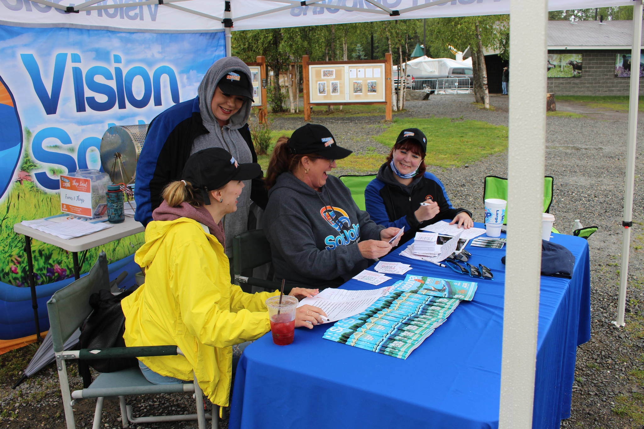 From left, Monique Burgin, Shanon Davis, Teresa Honrud and Sara Hondel of the Soldotna Chamber of Commerce add up the total amount of money spent as part of the Chamber's Soldotna Strong Shop Local campaign during Progress Days in Soldotna Creek Park on July 22, 2020. (Photo by Brian Mazurek/Peninsula Clarion)