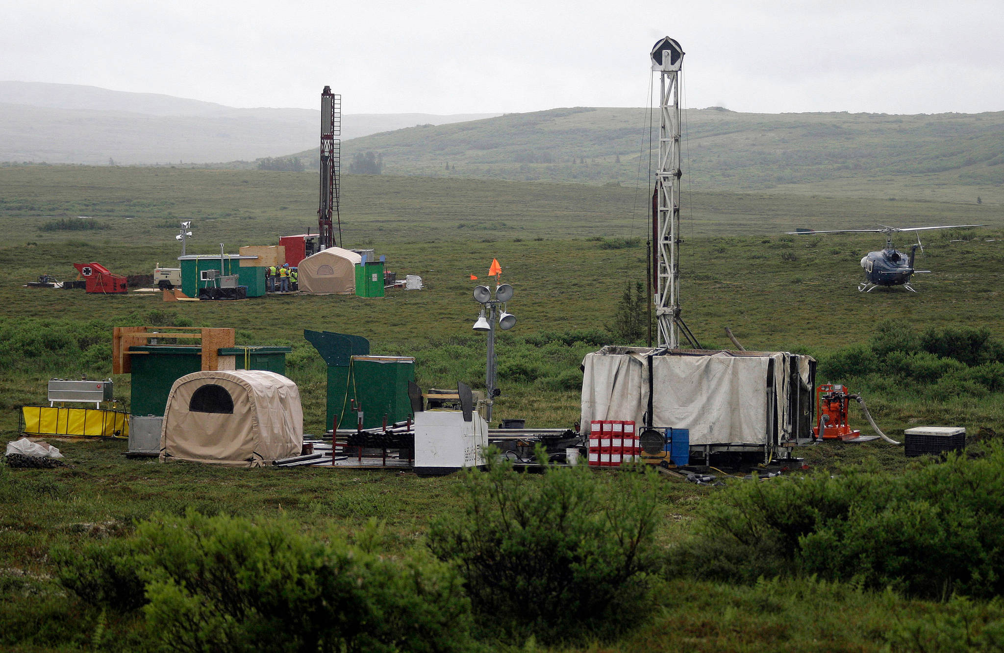 In this July 13, 2007, file photo, workers with the Pebble Mine project test drill in the Bristol Bay region of Alaska, near the village of Iliamma. The Pebble Limited Partnership, which wants to build a copper and gold mine near the headwaters of a major U.S. salmon fishery in southwest Alaska, says it plans to offer residents in the region a dividend. (AP Photo/Al Grillo, File)