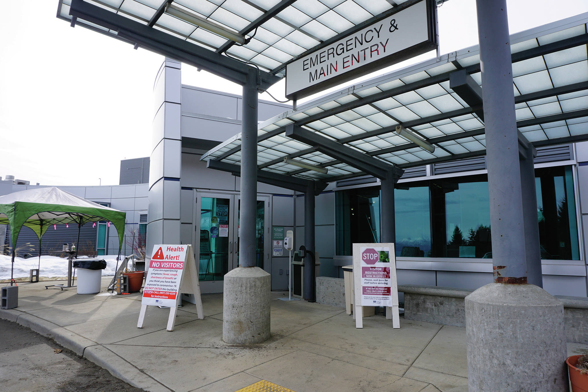 Signs on Saturday, March 28, 2020, at the main entrance to South Peninsula Hospital in Homer, Alaska, warn visitors not to enter until they have been met by hospital staff. (Photo by Michael Armstrong/Homer News)