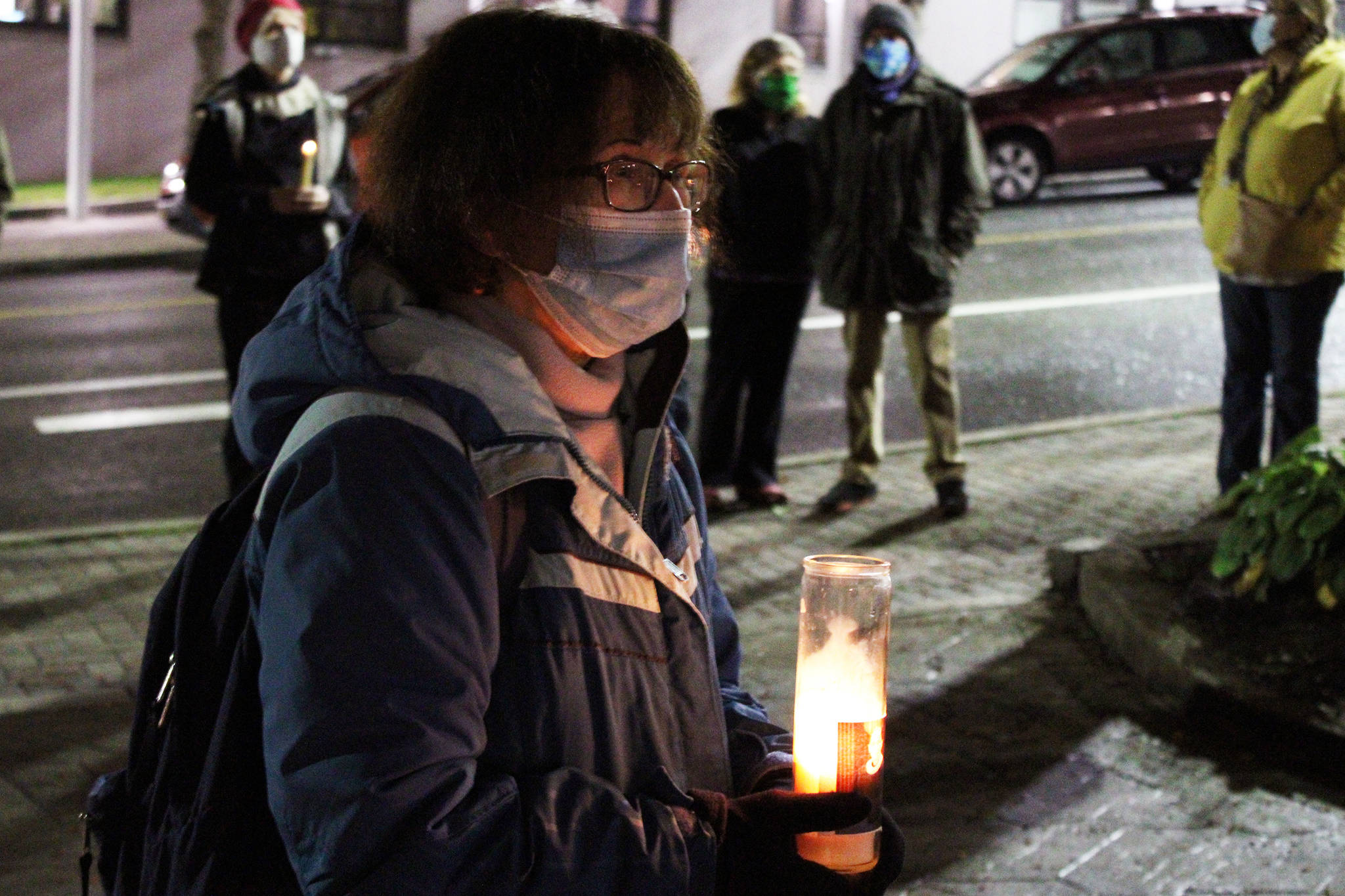 """Mary Szczepanski holds a candle decorated with a photo of the late Supreme Court Justice Ruth Bader Ginsburg at a candlelight vigil in downtown Juneau. """"I'm very inspired by everything she did and grateful that she was in our lives,"""" Szczepanski said. (Ben Hohenstatt / Juneau Empire)"""