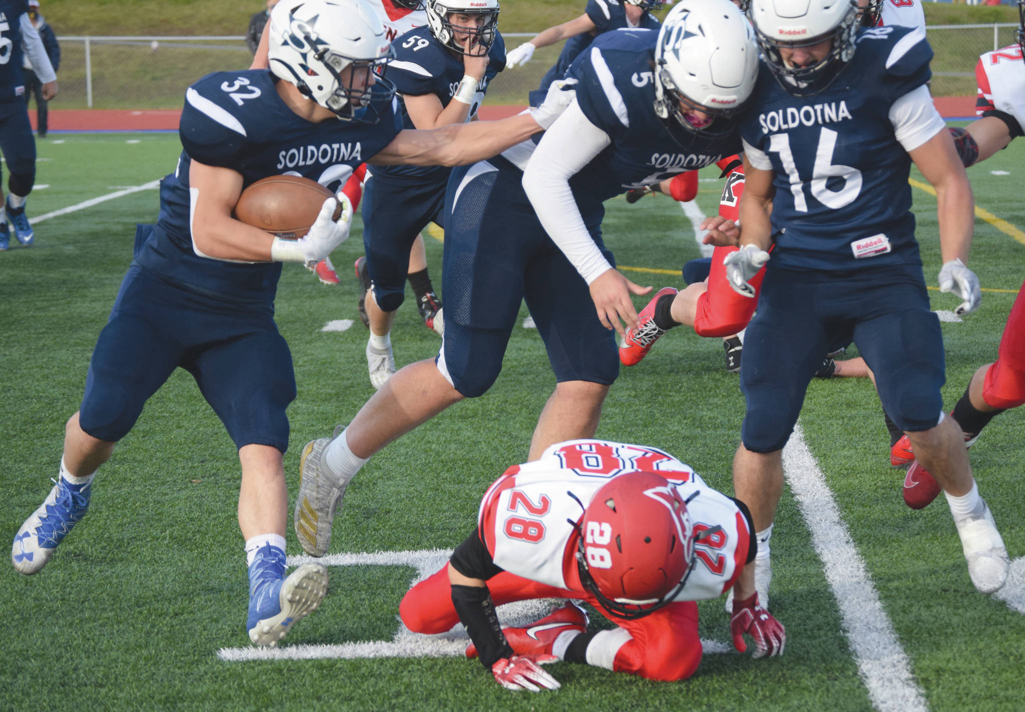 (Photo by Jeff Helminiak/Peninsula Clarion)Soldotna's Dennis Taylor follows the blocking of Brock Wilson and Austin Escott past Kenai Central's James Sparks on Friday, at Justin Maile Field in Soldotna.