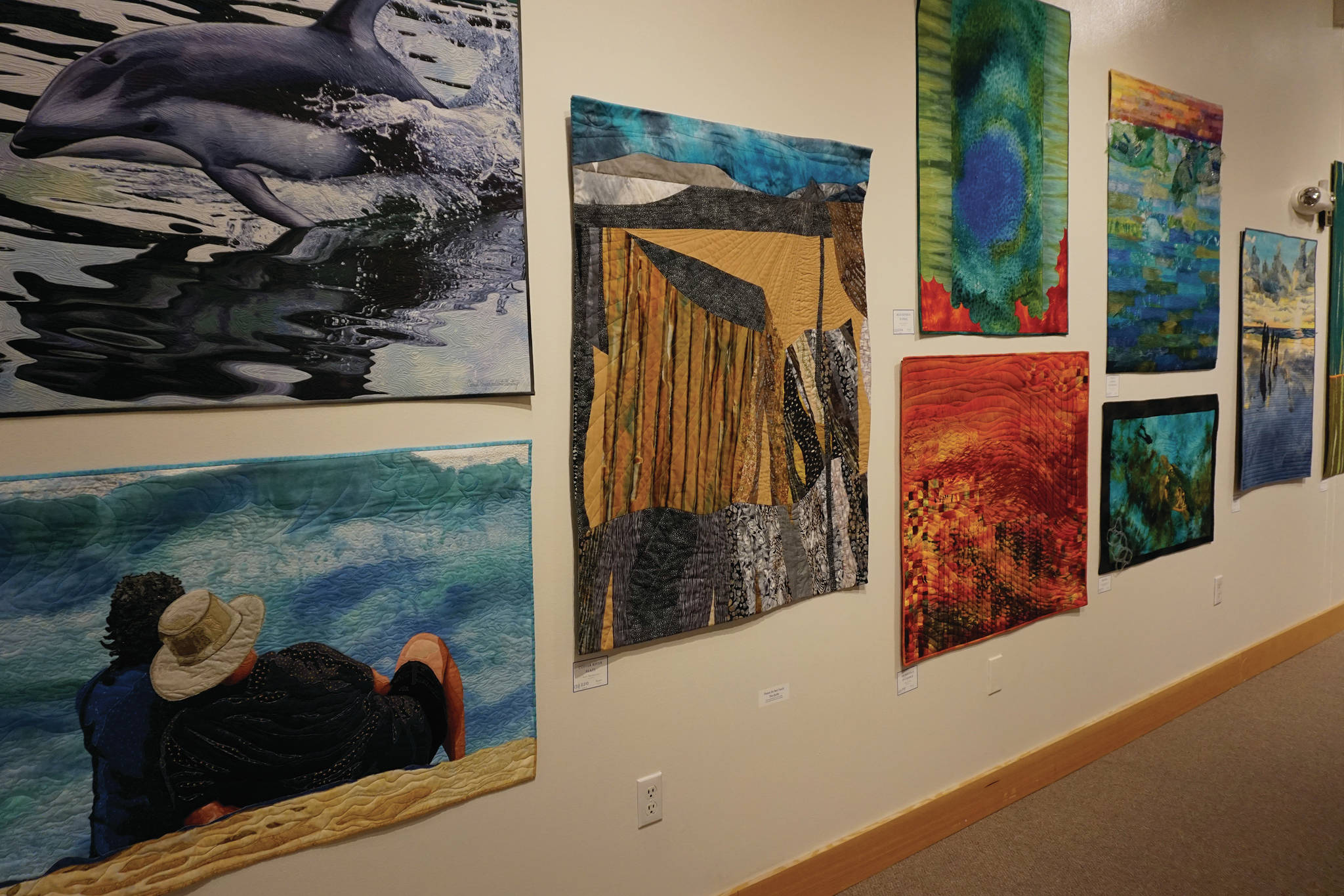 """Some of the 45 art quilts featured in """"Shifting Tides: Cloth in Convergence,"""" on exhibit from Oct. 9 to Nov. 28, 2020, at the Pratt Museum in Homer, Alaska. (Photo by Michael Armstrong/Homer News)"""