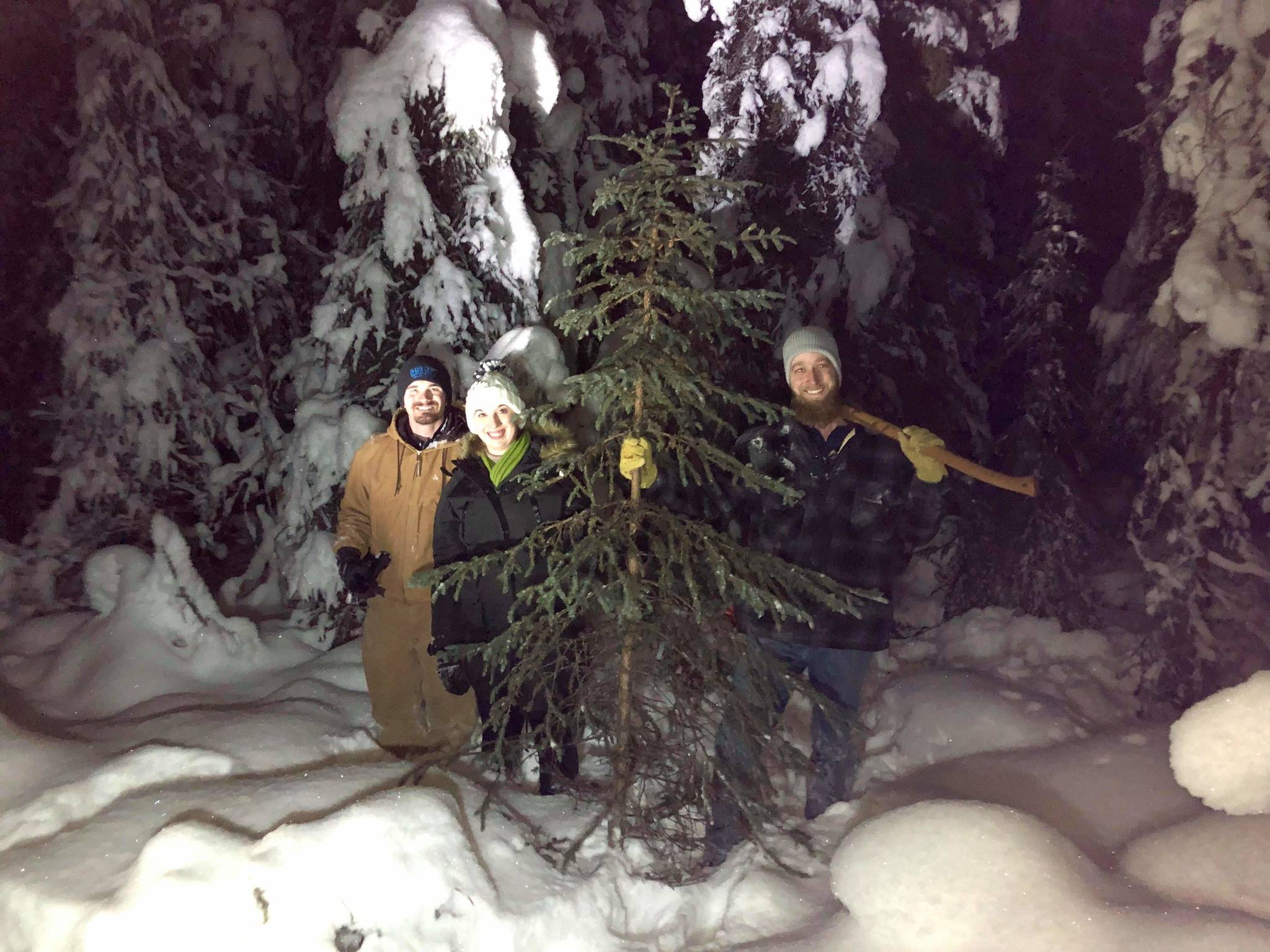 Ben Weagraff, Olivia Orth and Brian Mazurek stand next to a freshly cut black spruce off Funny River Road in Soldotna, Alaska on Dec. 8, 2019. (Photo by Victoria Peterson)