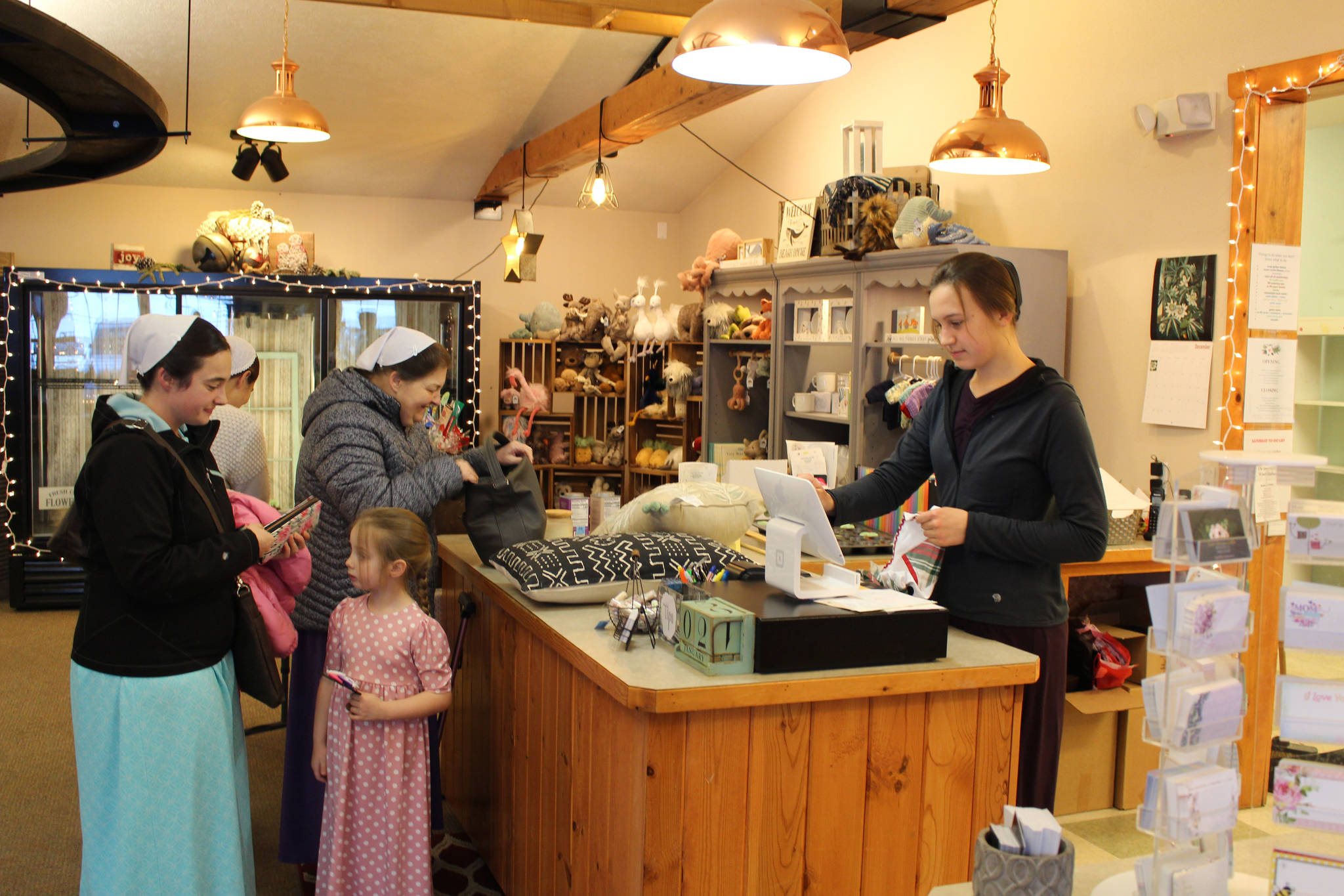 Brian Mazurek/Peninsula Clarion  From left, Sheryl Christner, Julia Christner, Ruby Eicher and Audrey Christner shop at Kate's Flowers and Gifts in Soldotna while Kate Mastre rings them up on Saturday.