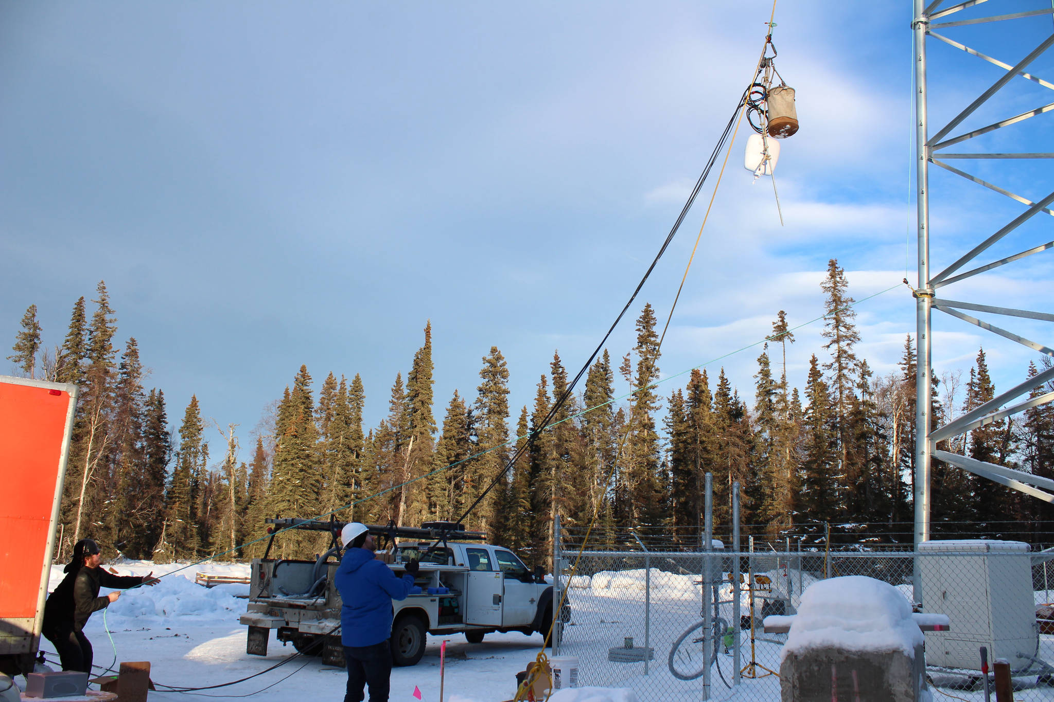 Bryan Stogsdill (left) and McKenzie McCarthy (right) hoist materials to the top of a communications tower on Thursday, Jan. 7 in Nikiski, Alaska. (Ashlyn O'Hara/Peninsula Clarion)