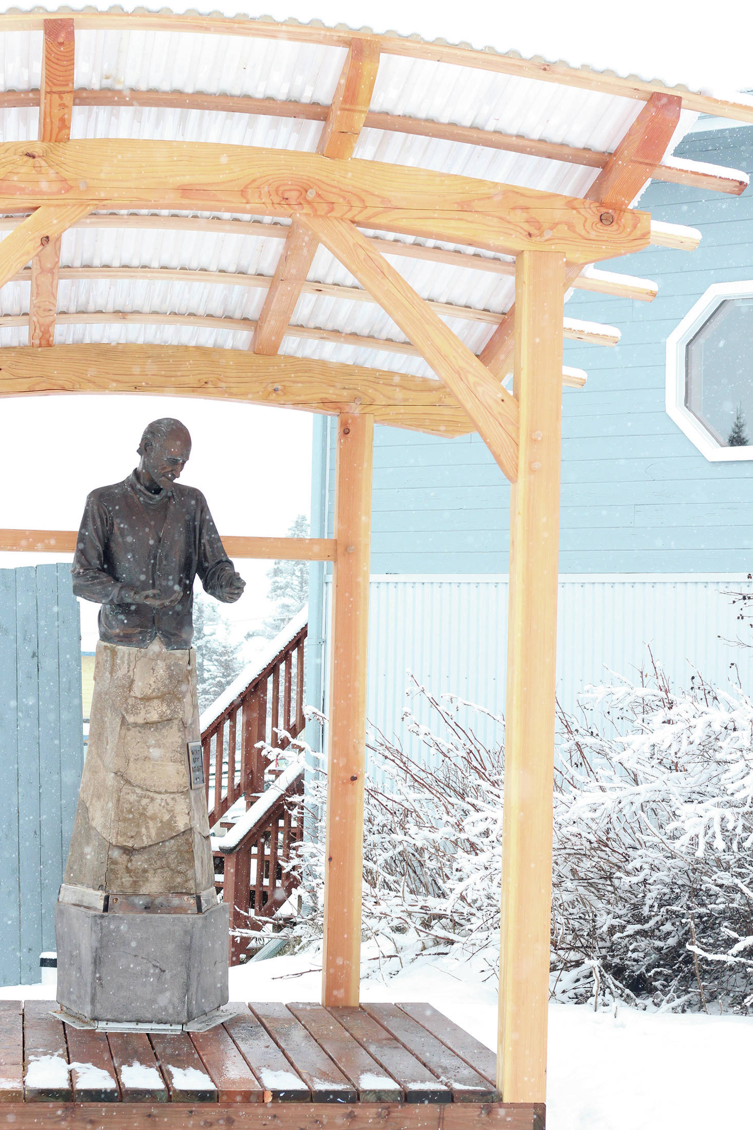 A statue of Brother Asaiah rests under a protective wooden structure on Thursday, Feb. 18, 2021 outside KBBI Public Radio in Homer, Alaska. (Photo by Megan Pacer/Homer News)