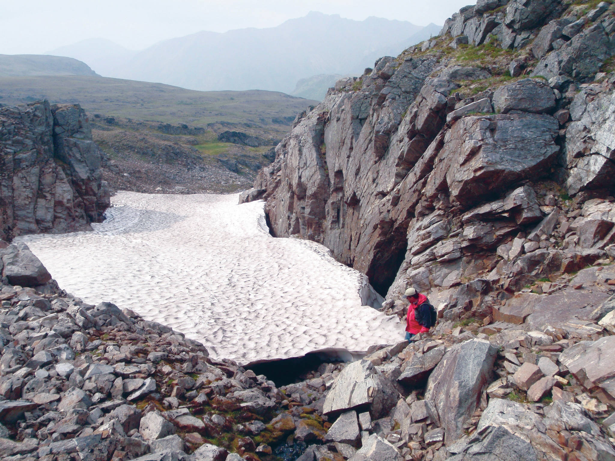 Archaeologist examining ice patch in Lake Clark National Park and Preserve. (Photo by National Park Service)
