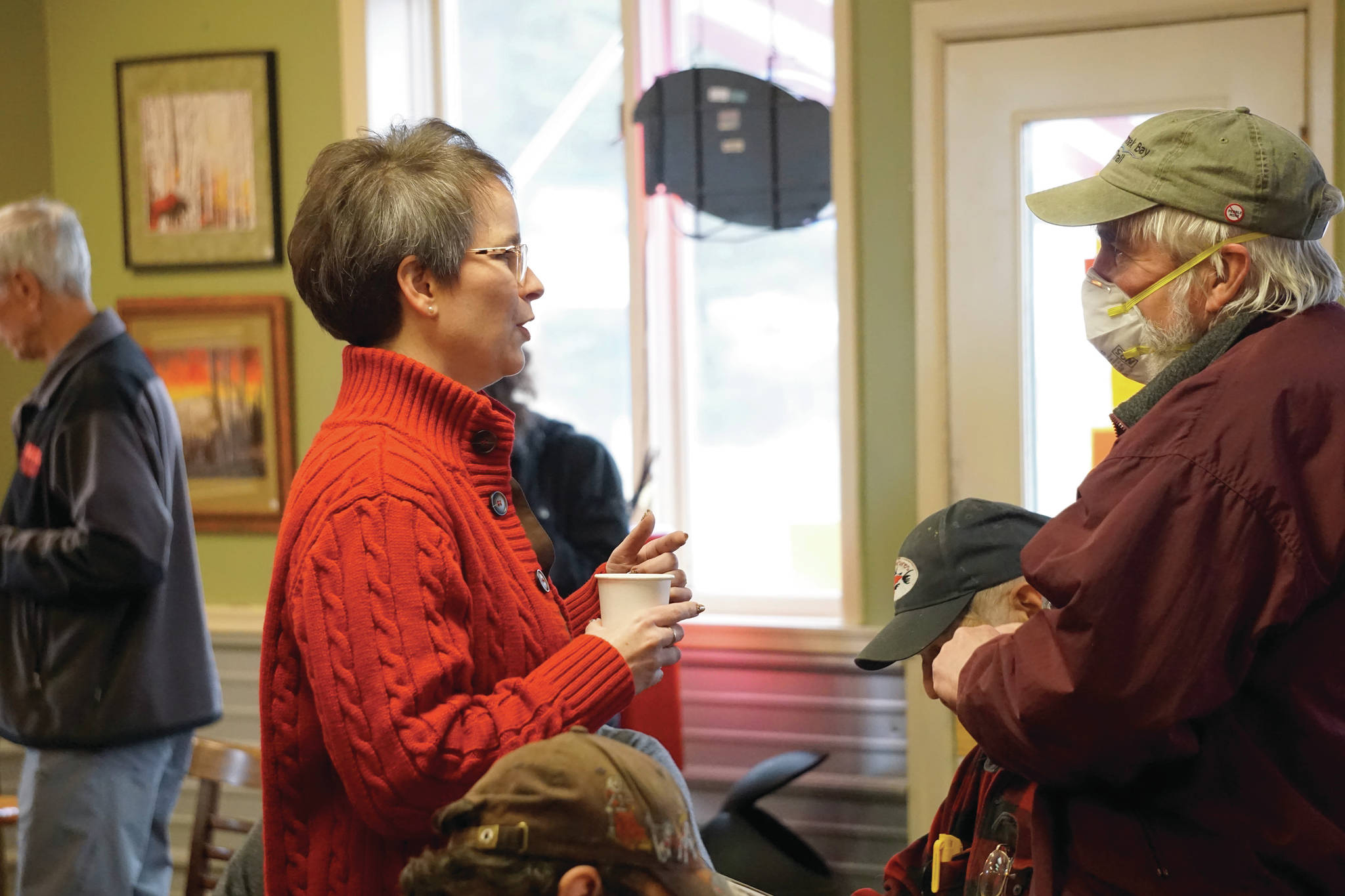 Rep. Sarah Vance, R-Homer, left, speaks with Robert Archibald, right, before holding a town hall meeting on Monday, March 29, 2021, at Captain's Coffee in Homer, Alaska. Archibald was only one of four people who wore face masks at the event of about 55 people. (Photo by Michael Armstrong/Homer News)