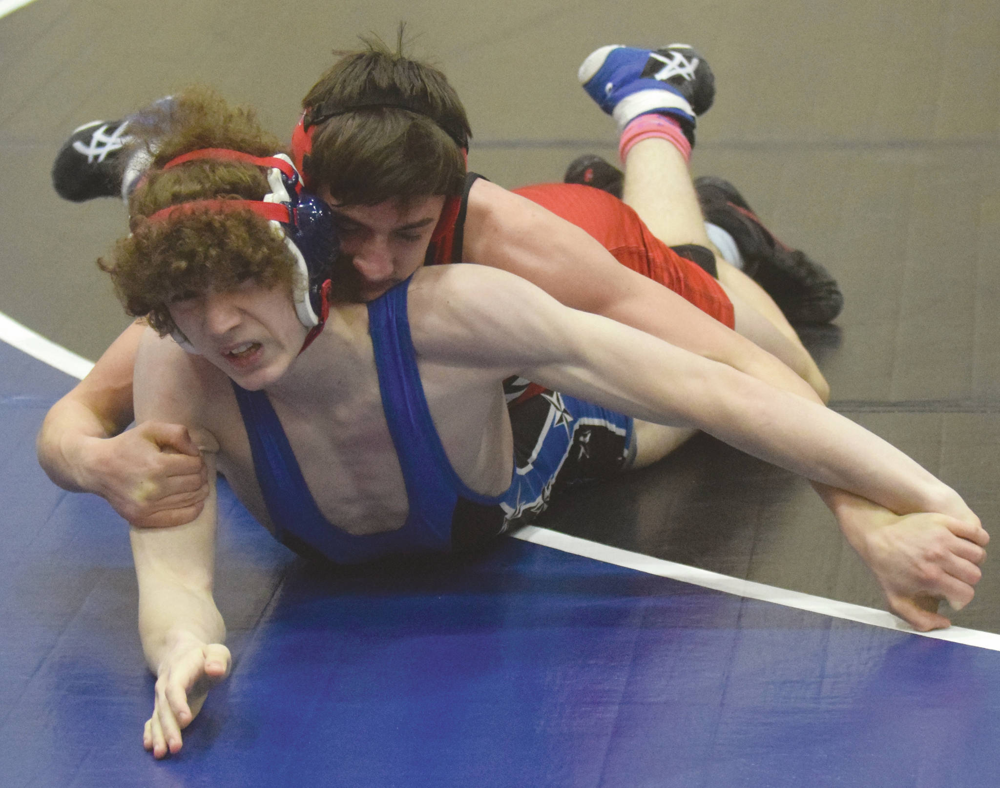 Kenai Central's Owen Whicker controls Soldotna's Cassius Miller on the way to a 7-5 victory Friday, April 2, 2021, at Soldotna High School in Soldotna, Alaska. (Photo by Jeff Helminiak/Peninsula Clarion)