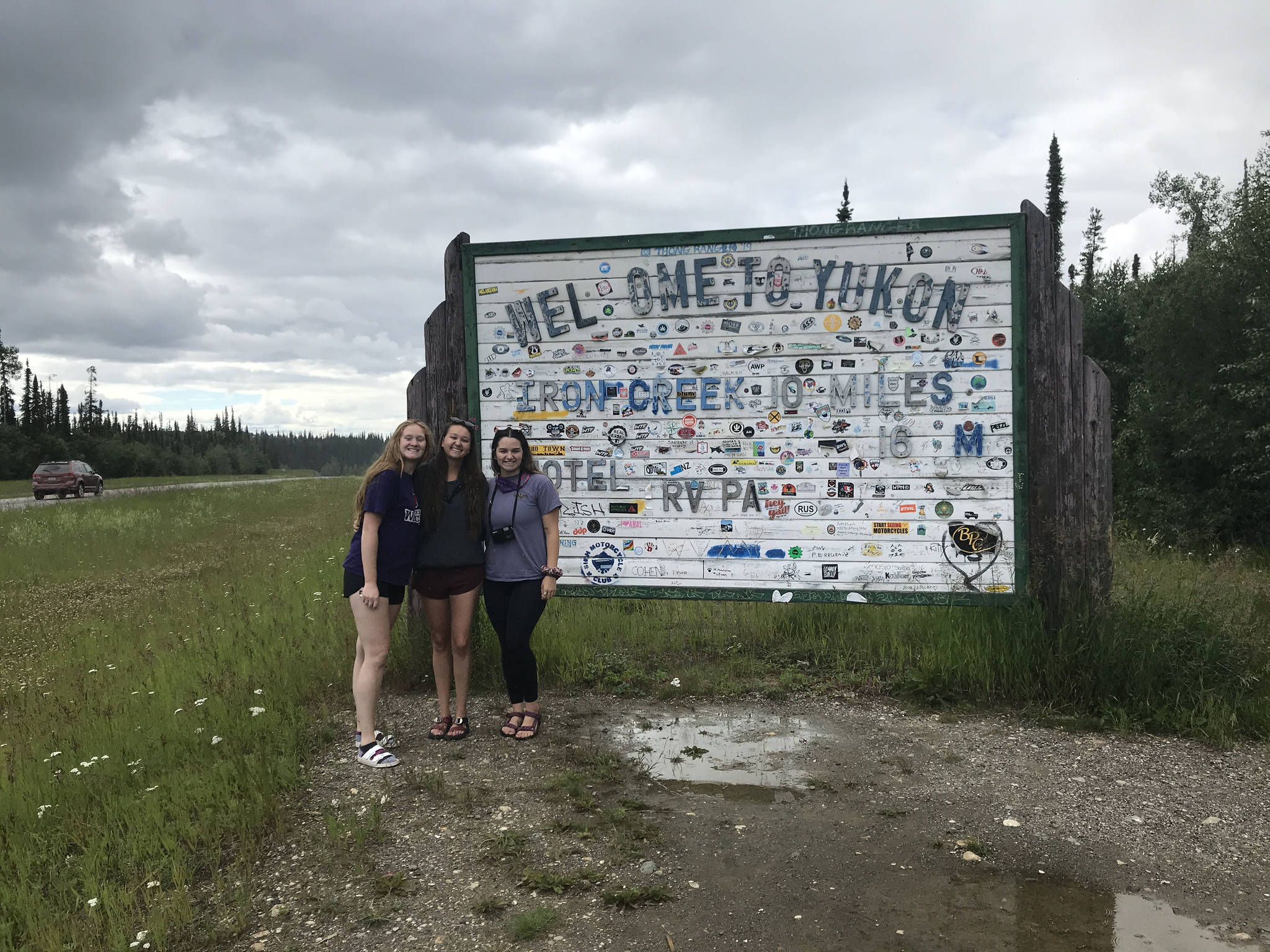 From left to right: Camille Botello, Emma Schoonover and Grace Thompson-Johnston stand in front of a sign welcoming them to the Yukon territory in Canada as they make their way up the Alaska Highway on July 16, 2020. (Photo provided)
