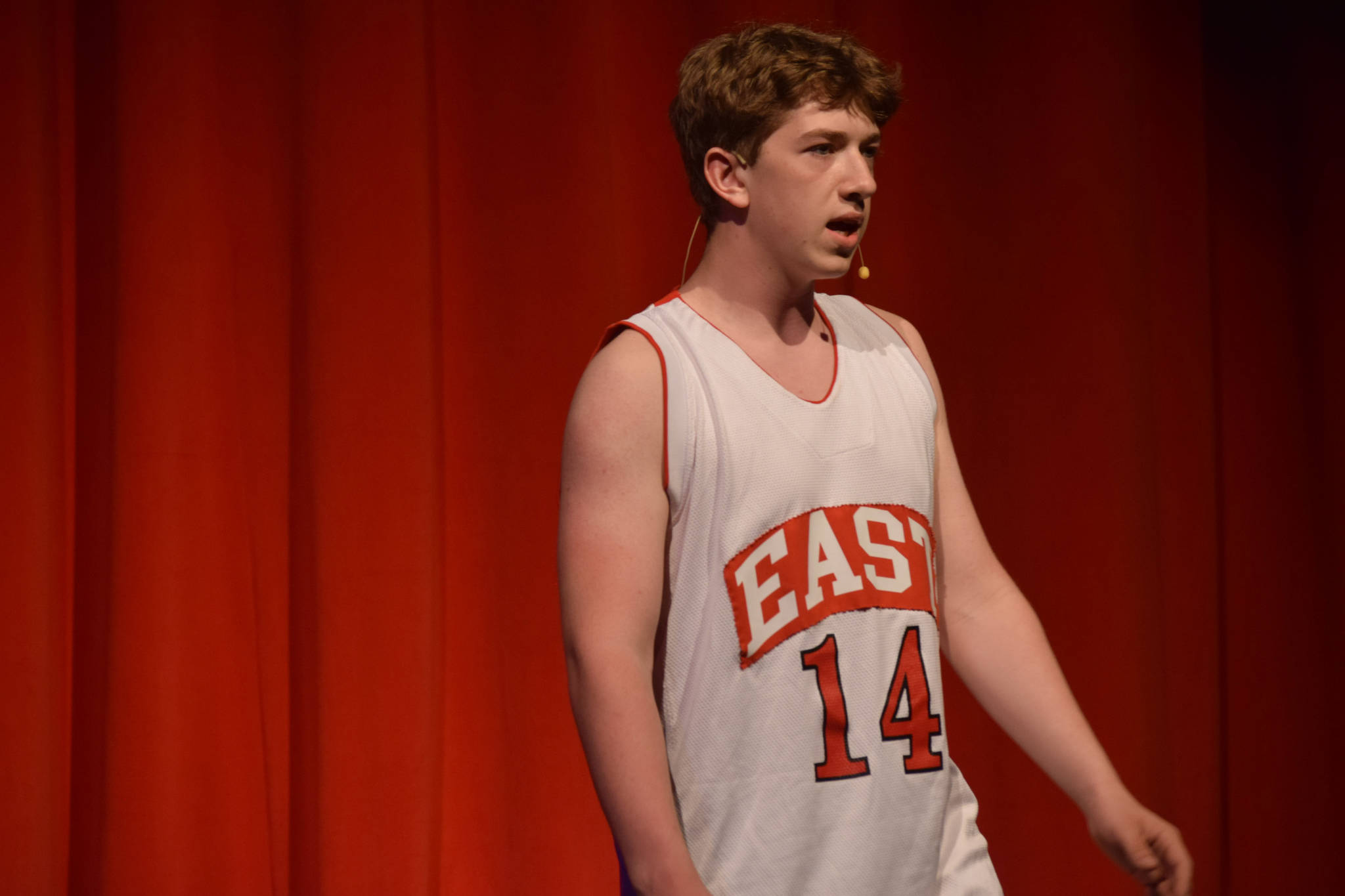"""Braeden Porter sings onstage as his character Troy Bolton in the Nikiski Middle/High School's spring production of """"High School Musical"""" in Nikiski, Alaska, on Wednesday May 5, 2021. (Camille Botello / Peninsula Clarion)"""