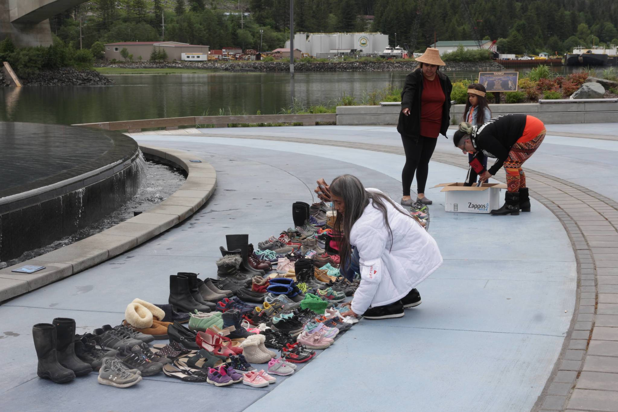 Michael S. Lockett / Juneau Empire Juneau residents place hundreds of pairs of children's shoes in front of the statue at Mayor Bill Overstreet Park on Saturday as they mourned for the 215 dead children uncovered at a residential school in Canada.