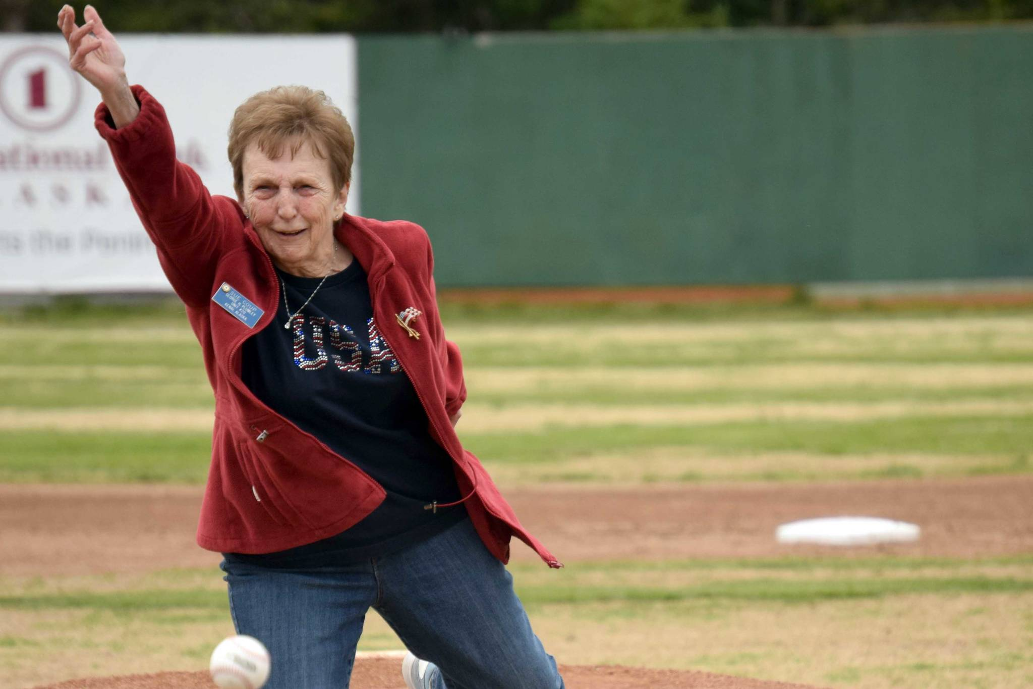 Nikiski's Sue Coup throws out the first pitch at a ceremony honoring former Twins head coach and general manager Lance Coz on Saturday, July 3, 2021, at Coral Seymour Memorial Park in Kenai, Alaska. (Photo by Jeff Helminiak/Peninsula Clarion)
