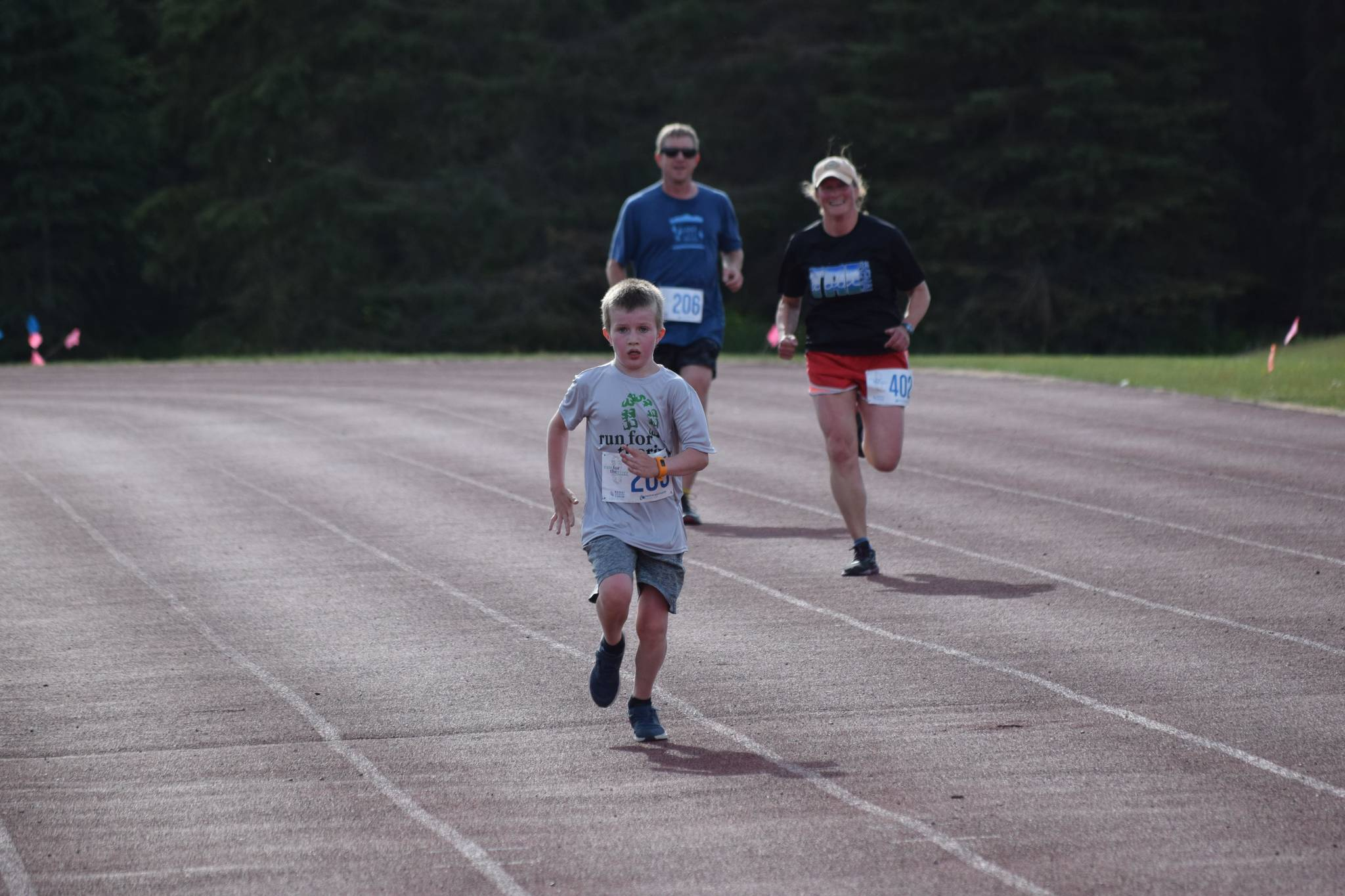 Gus Reimer crosses the finish line in front of Adam Reimer and Julie Laker during the first race of the Salmon Run Series at Skyview Middle School on Wednesday, July 7, 2021. (Camille Botello / Peninsula Clarion)