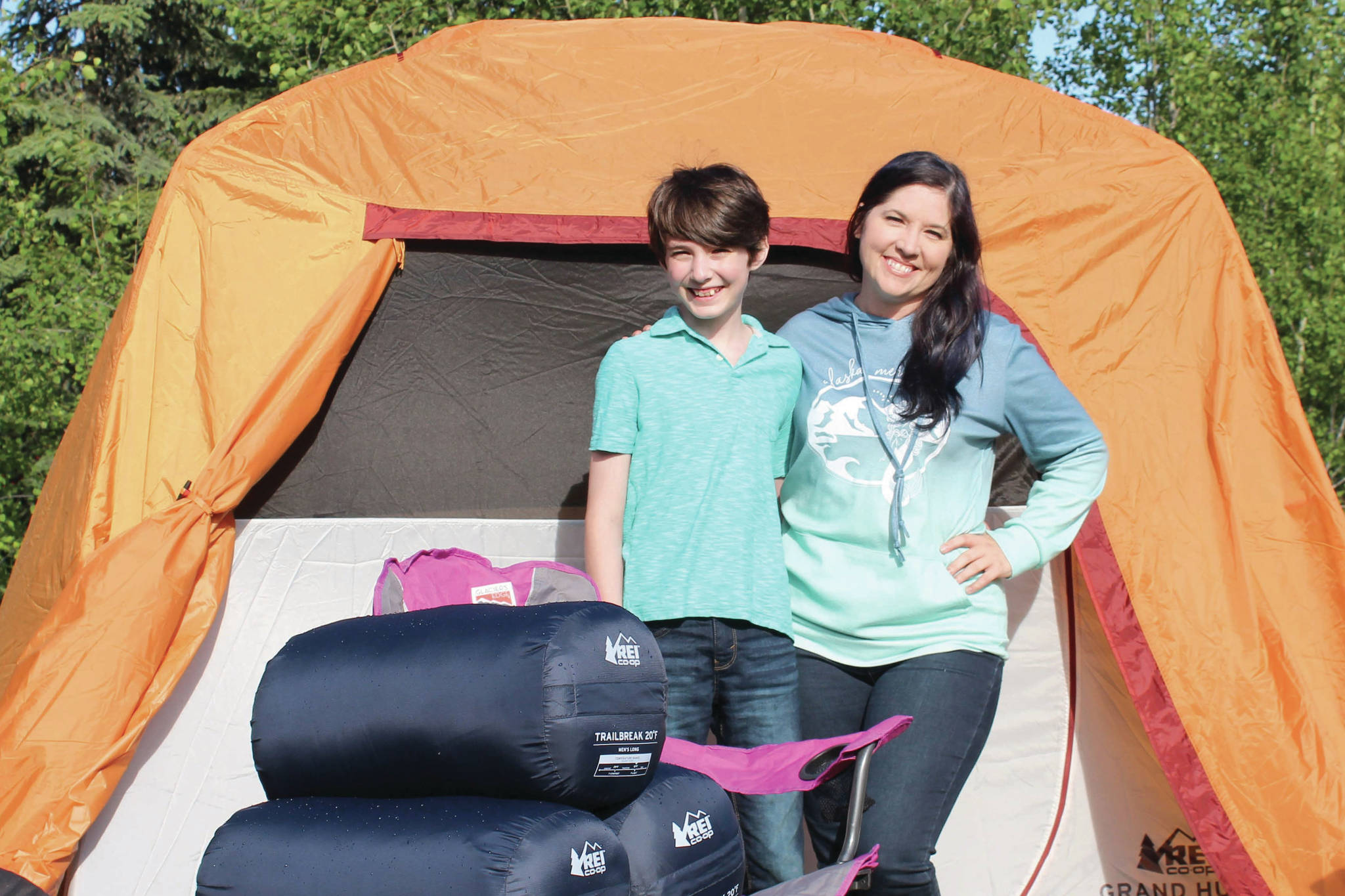 Koebryn and Summer Lazenby stand in front of camping gear at Summer's house on Tuesday, July 13, 2021 near Soldotna, Alaska. (Ashlyn O'Hara/Peninsula Clarion)