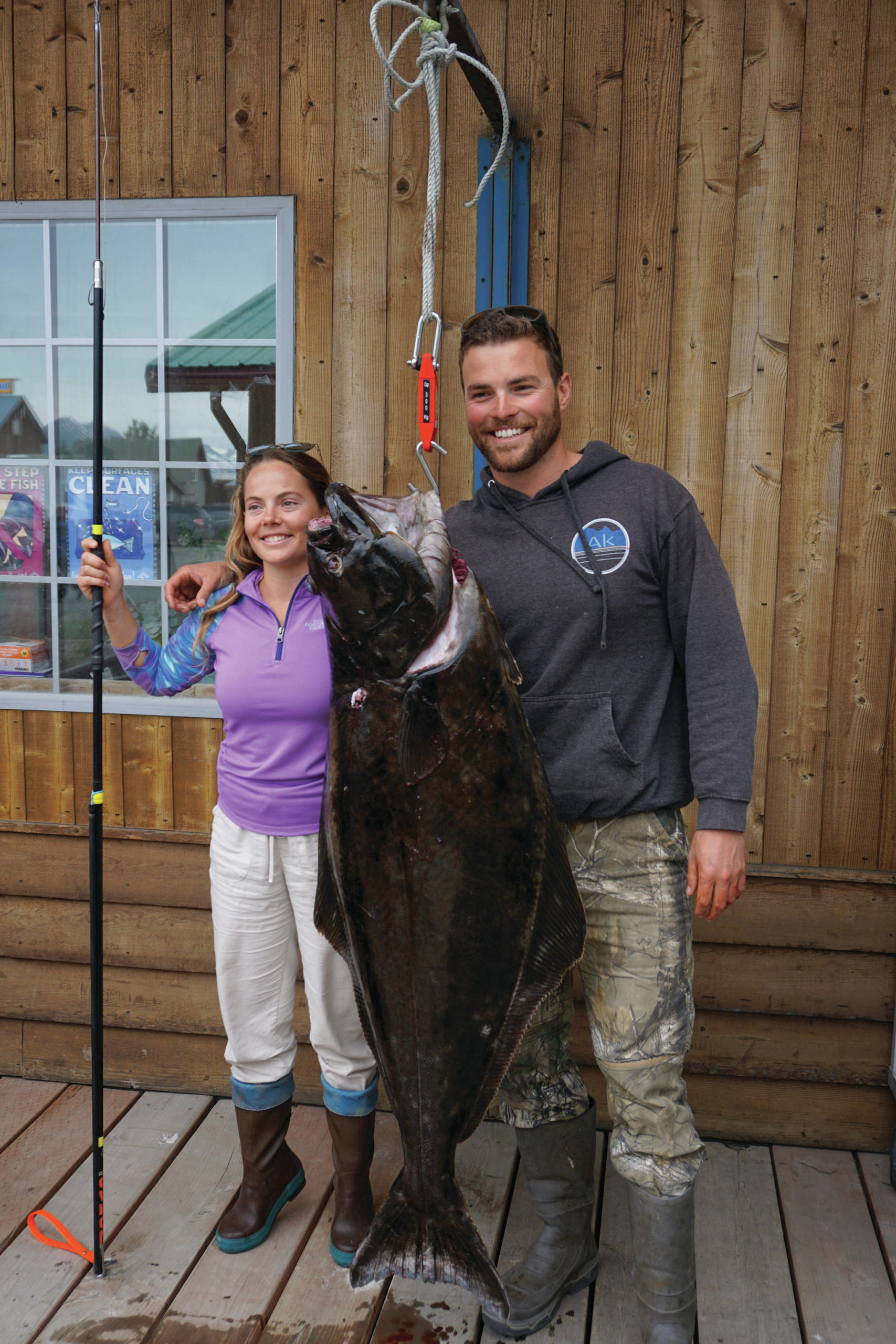 Lisa Stengel of Fort Lauderdale, Florida, poses for a photo with Capt. Brian Reid of the Castle Cape on Monday, July 12, 2021, at Coal Point Seafoods in Homer, Alaska, with a 71.4-pound halibut that she caught with a pole spear while free diving in Kachemak Bay. Stengel and her party went on a spearfishing expedition with Reid of Coldwater AK. (Photo by Michael Armstrong/Homer News)