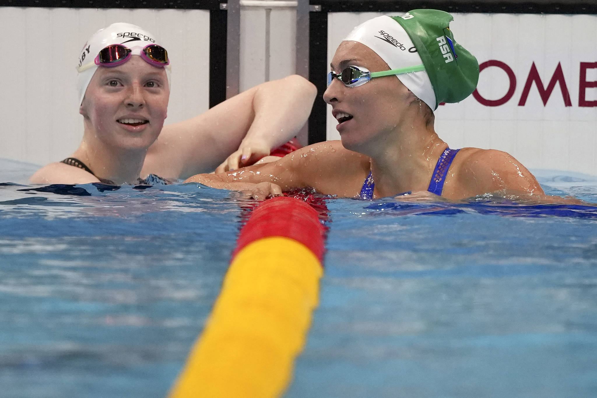 Lydia Jacoby, left, of the United States congratulates Tatjana Schoenmaker of South Africa after their heat in the women's 100-meter breaststroke at the 2020 Summer Olympics, Sunday, July 25, 2021, in Tokyo, Japan. (AP Photo/Matthias Schrader)