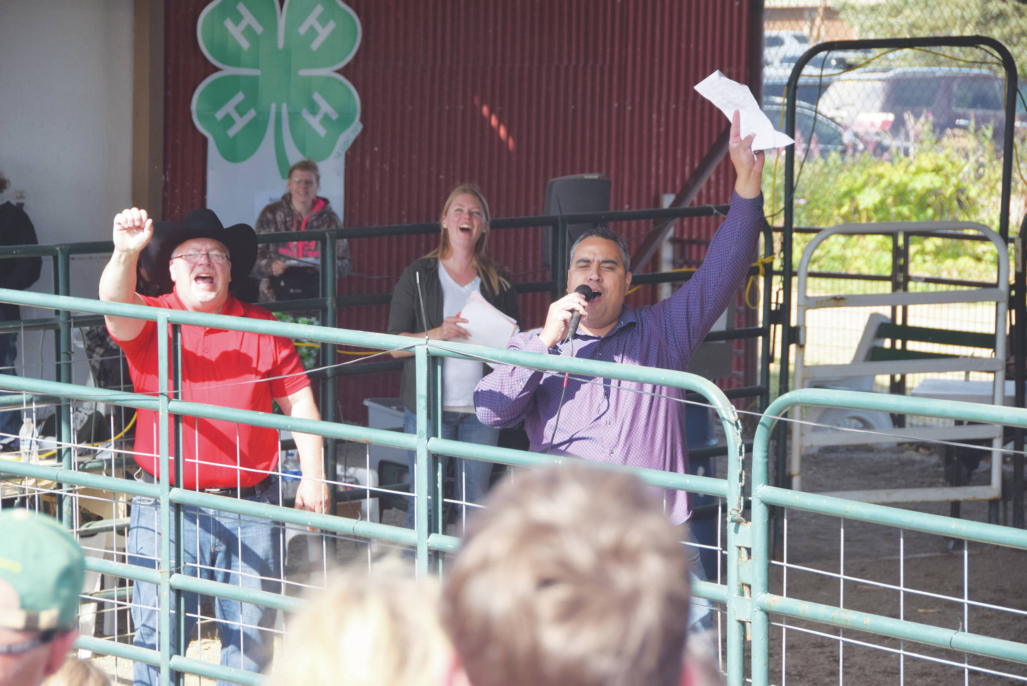 Peninsula Clarion file Auctioneers Andy Kriner, left, and Rayne, Reynolds celebrate a successful sale during the 4-H Junior Market Livestock Auction at the Kenai Peninsula Fair on Aug. 17, 2019 at the fairgrounds in Ninilchik.