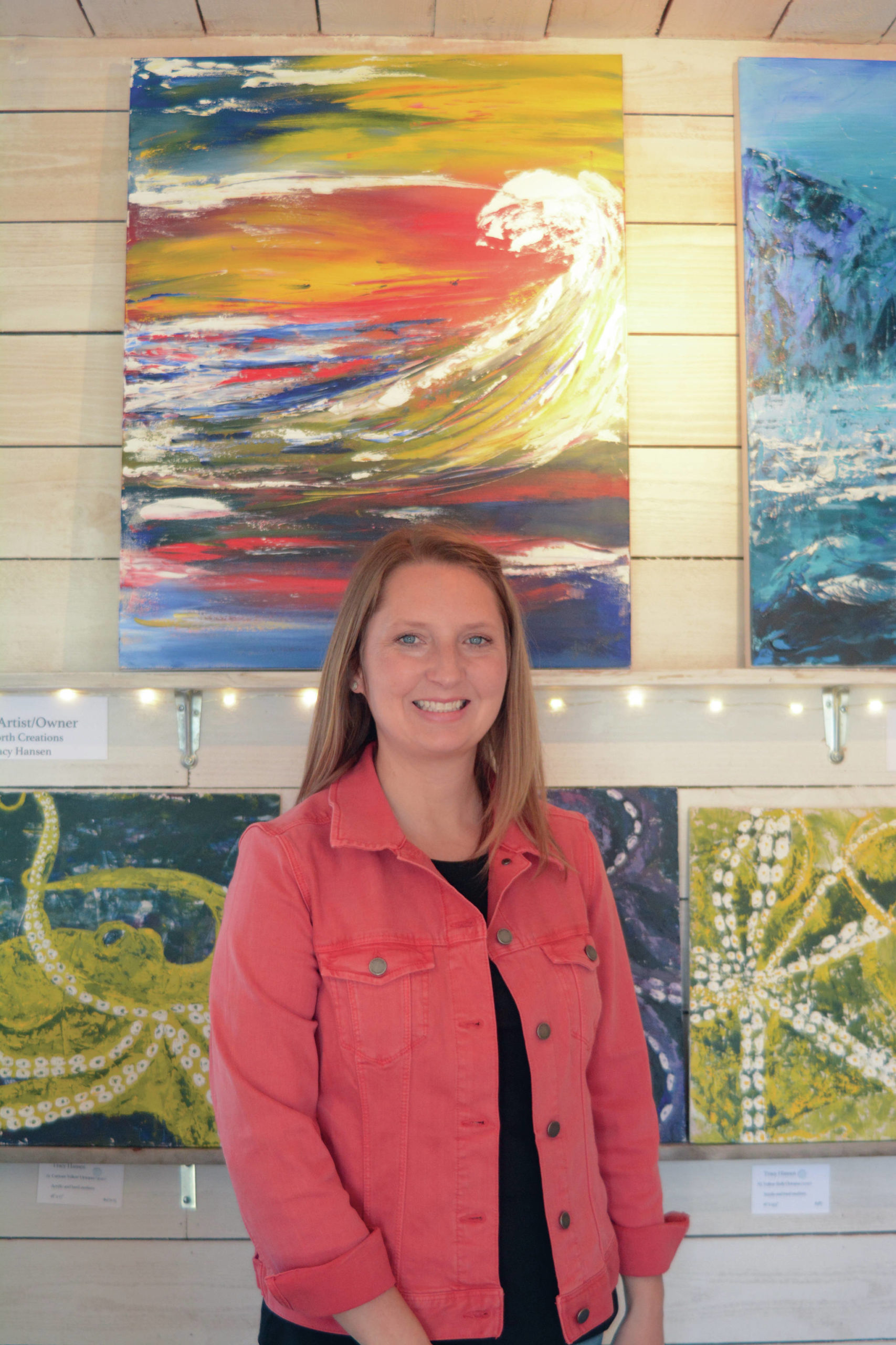 Tracy Hansen poses for a photo in front of her paintings at her Ocean Drive shop, 59 North, on Tuesday, Aug. 10, 2021, in Homer, Alaska. (Photo by Michael Armstrong/Homer News)
